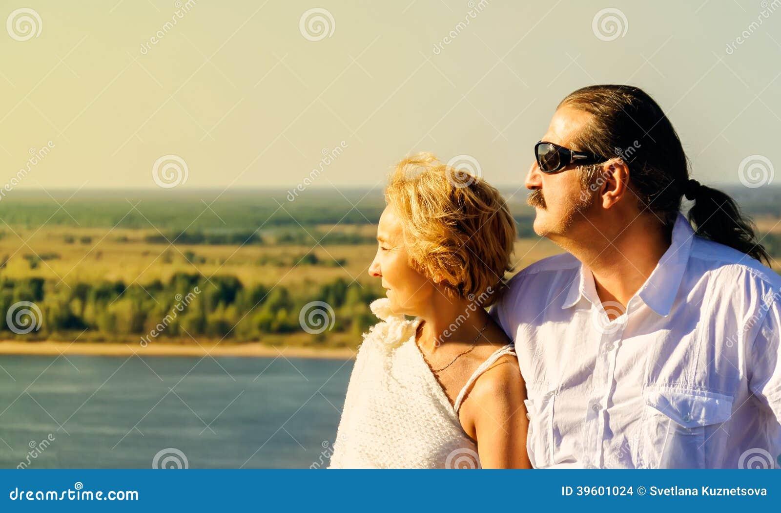 Το ώριμο ζευγάρι κοιτάζει μακρυά προς τον ερχόμενο ήλιο