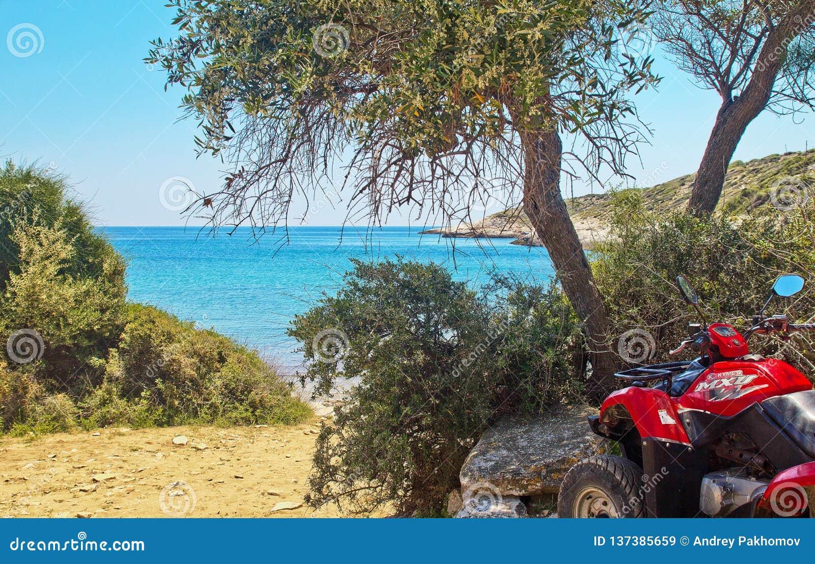 Το ATV σταθμεύουν στην ακτή στο νησί Thassos, Ελλάδα άποψη του όμορφου τοπίου