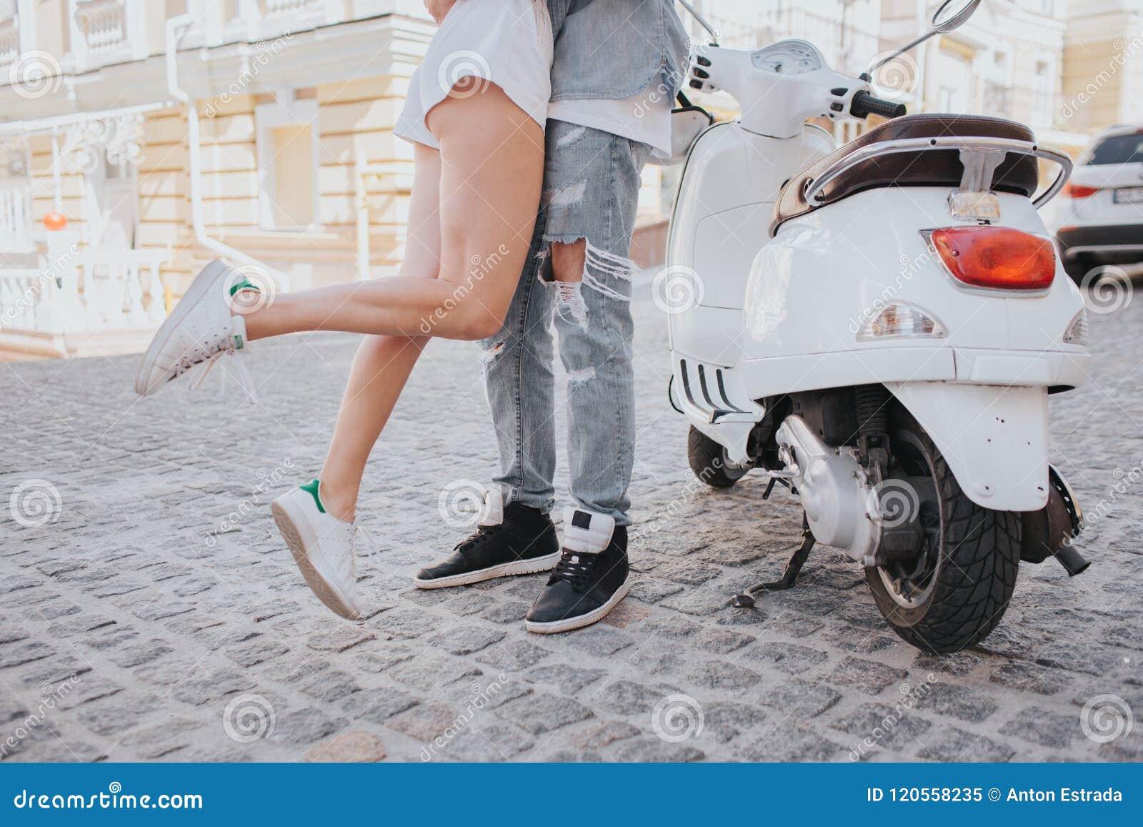 Το Gril πηδά κοντά στον τύπο Τα πόδια της είναι στον αέρα Στέκονται εκτός από τη μοτοσικλέτα στη μέση της οδού Έχουν το α