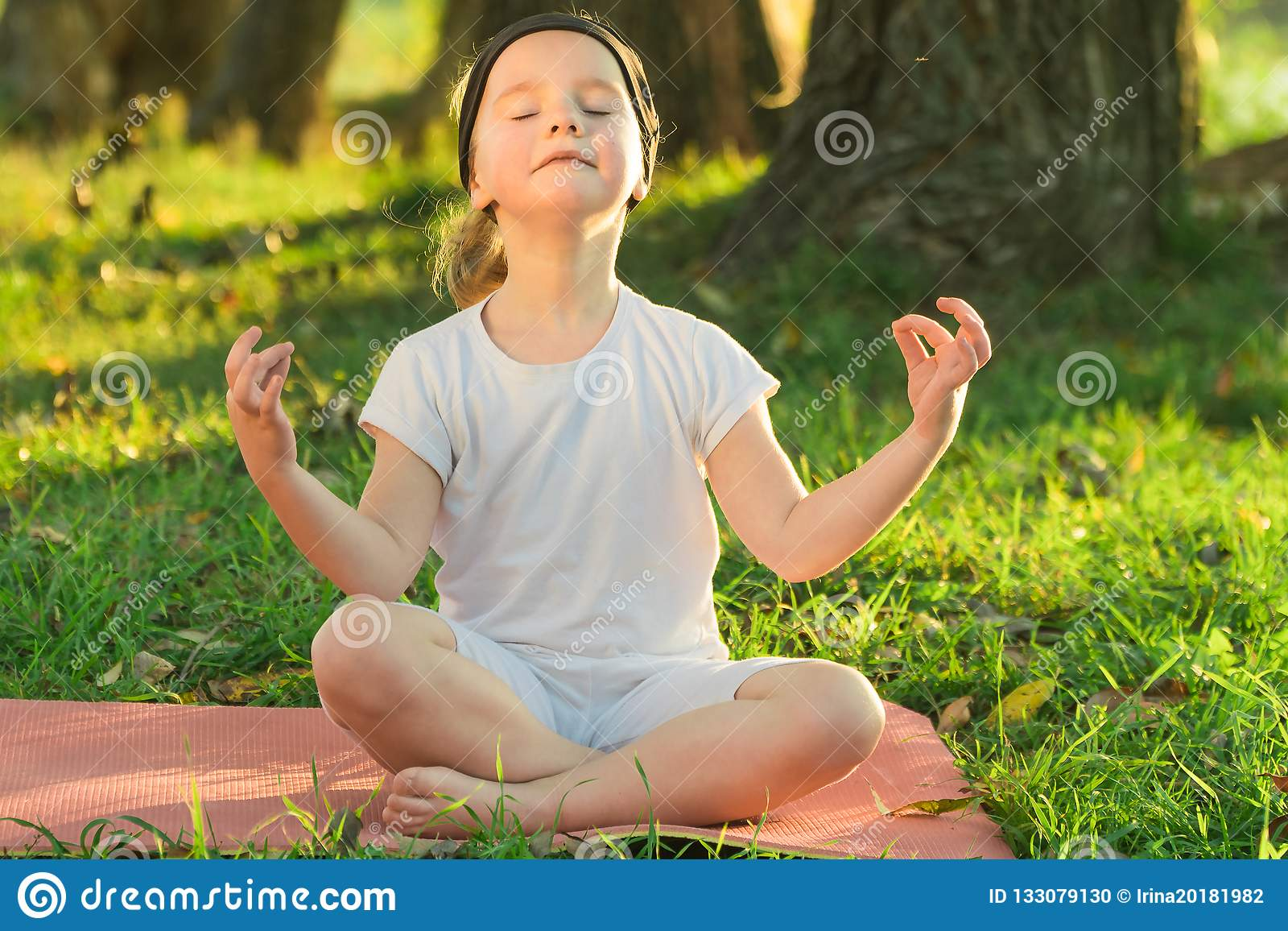 Το Lotus γιόγκας μωρών θέτει μια γιόγκα άσκησης παιδιών υπαίθρια