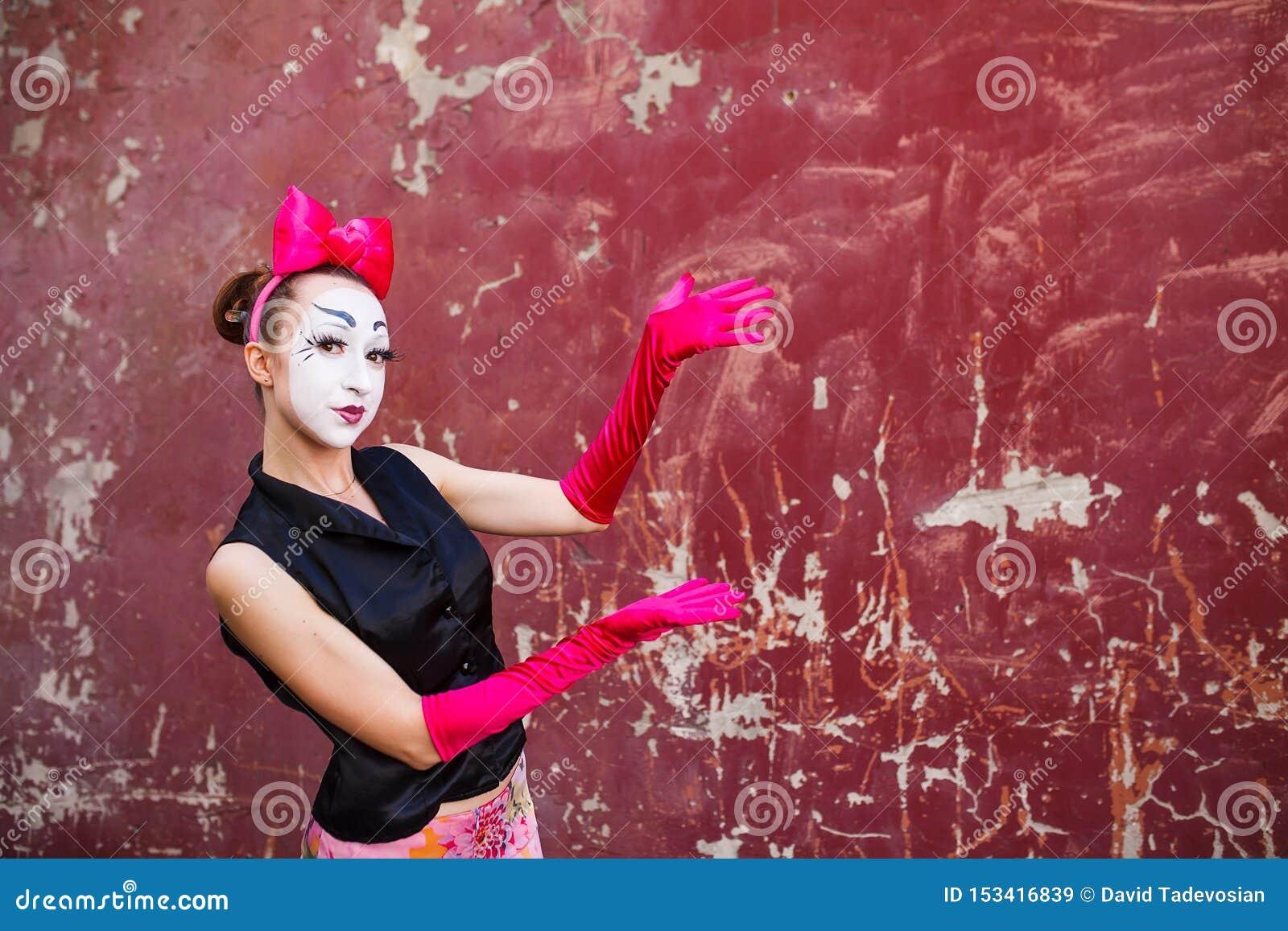 Το Mime δείχνει ένα δάχτυλο στο κέντρο σε ένα κλίμα ενός κόκκινου τοίχου