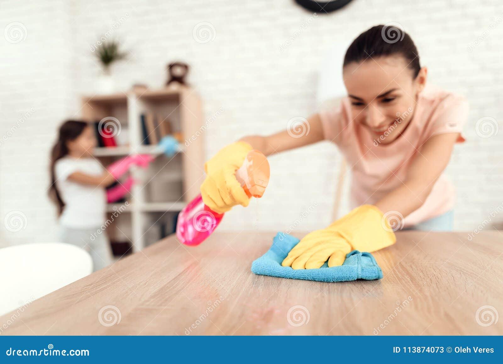 Το Mom και η κόρη καθαρίζουν στο σπίτι Σκουπίστε τα ράφια και τον πίνακα