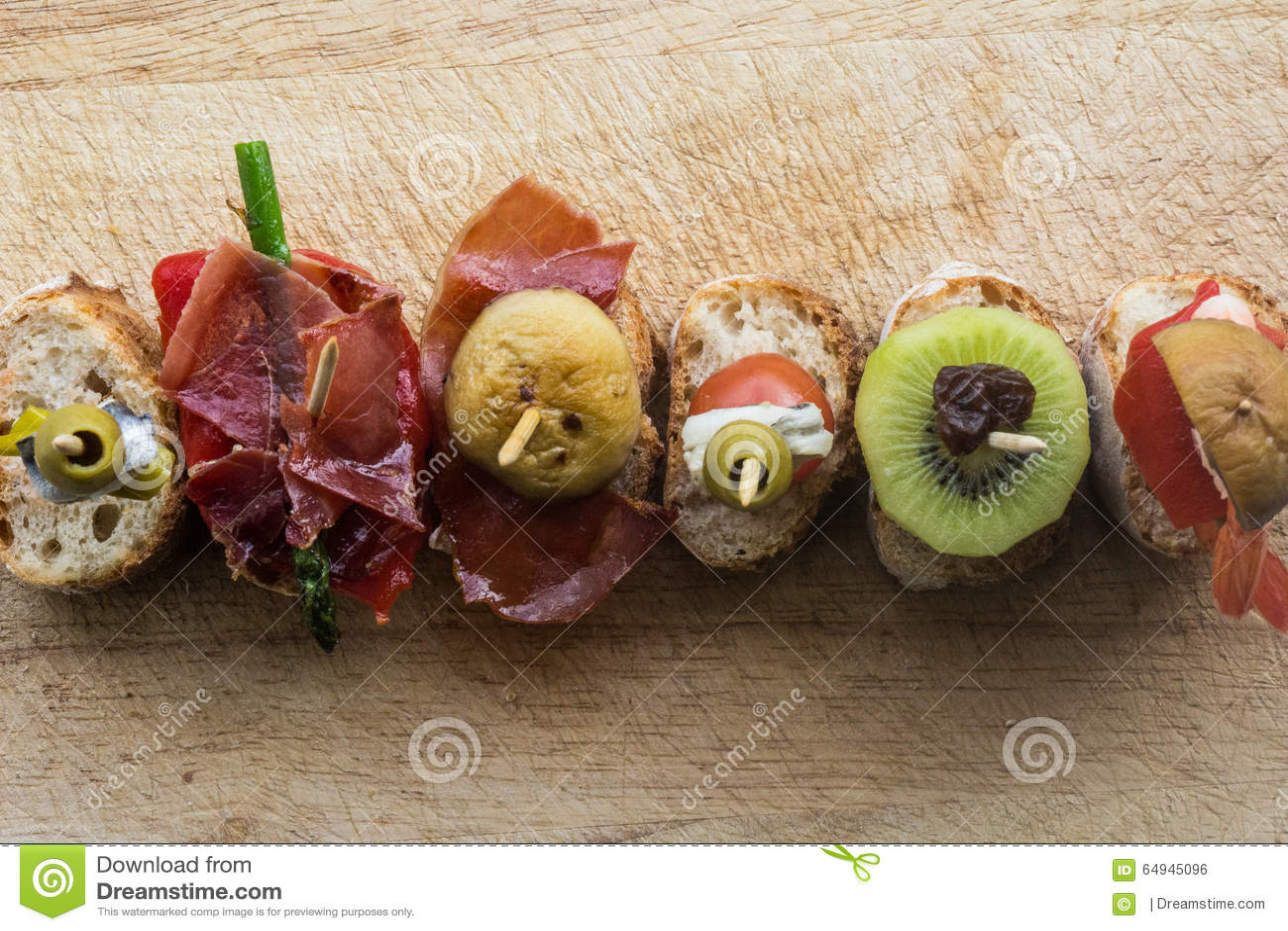 Το Pintxo έθεσε: Η ελιά, αντσούγια, ντομάτα κερασιών, ακτινίδιο, σταφίδα, θεράπευσε το ζαμπόν, μανιτάρι, ψωμί σε έναν αγροτικό πί