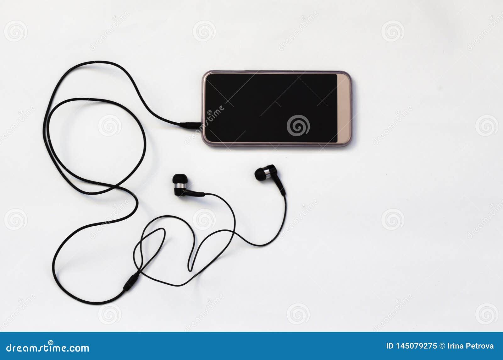 Το Smartphone με την κενή οθόνη συνδέει με τα ακουστικά με το σπειροειδές κα