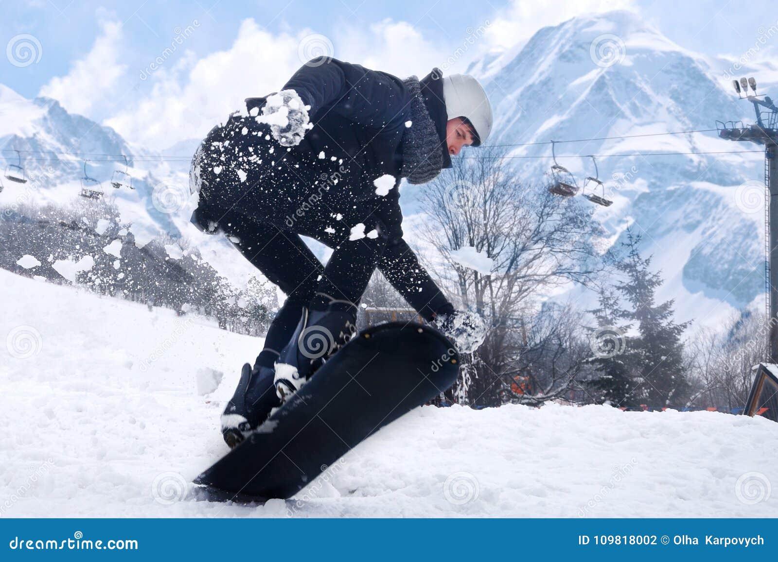 Το Snowboarder πηδά με το σνόουμπορντ από το snowhill Τοπίο βουνών άλματος ατόμων στο υπόβαθρο Να κάνει σκι Snowboarder μέσα υψηλ