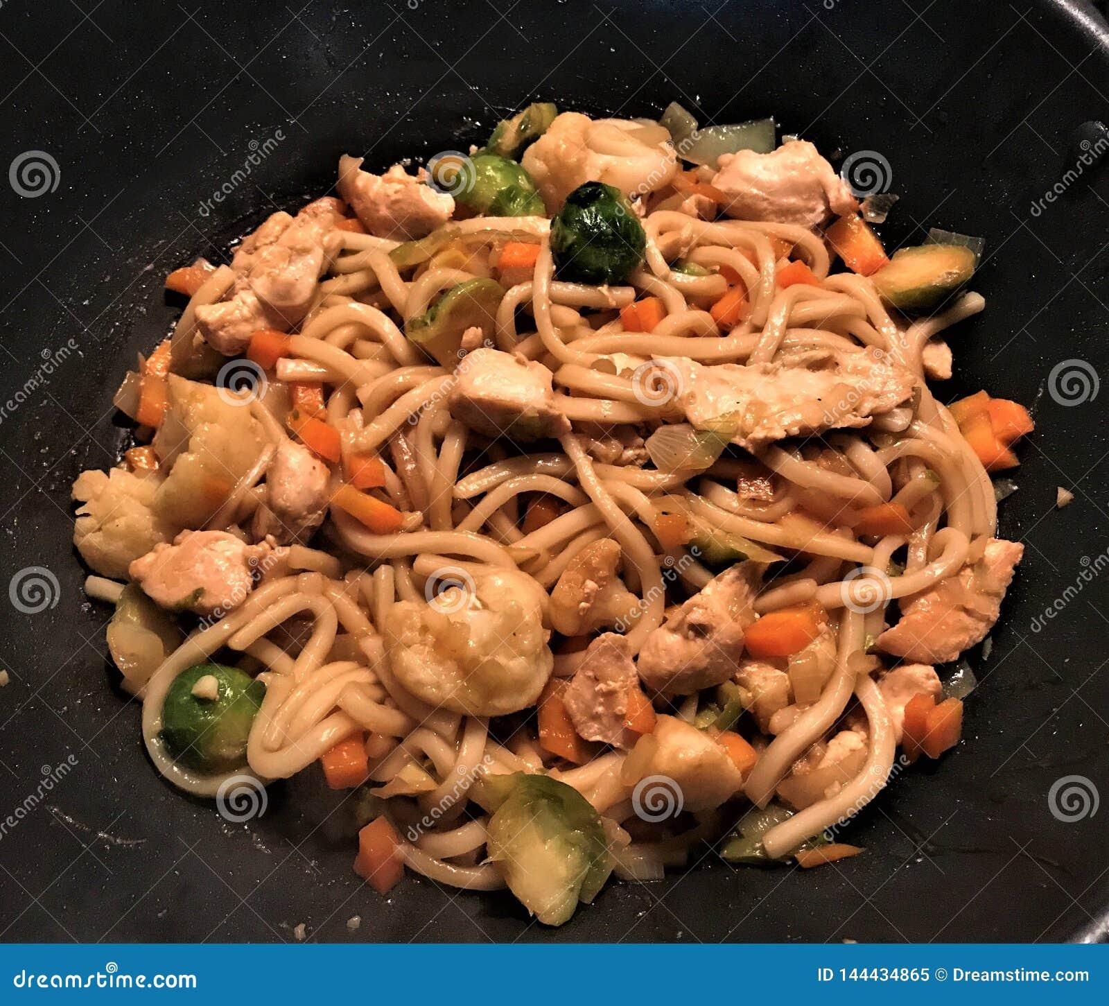 Το Udon Mi με το κοτόπουλο και τα λαχανικά ανακατώνουν τα τηγανητά στη σάλτσα teriyaki