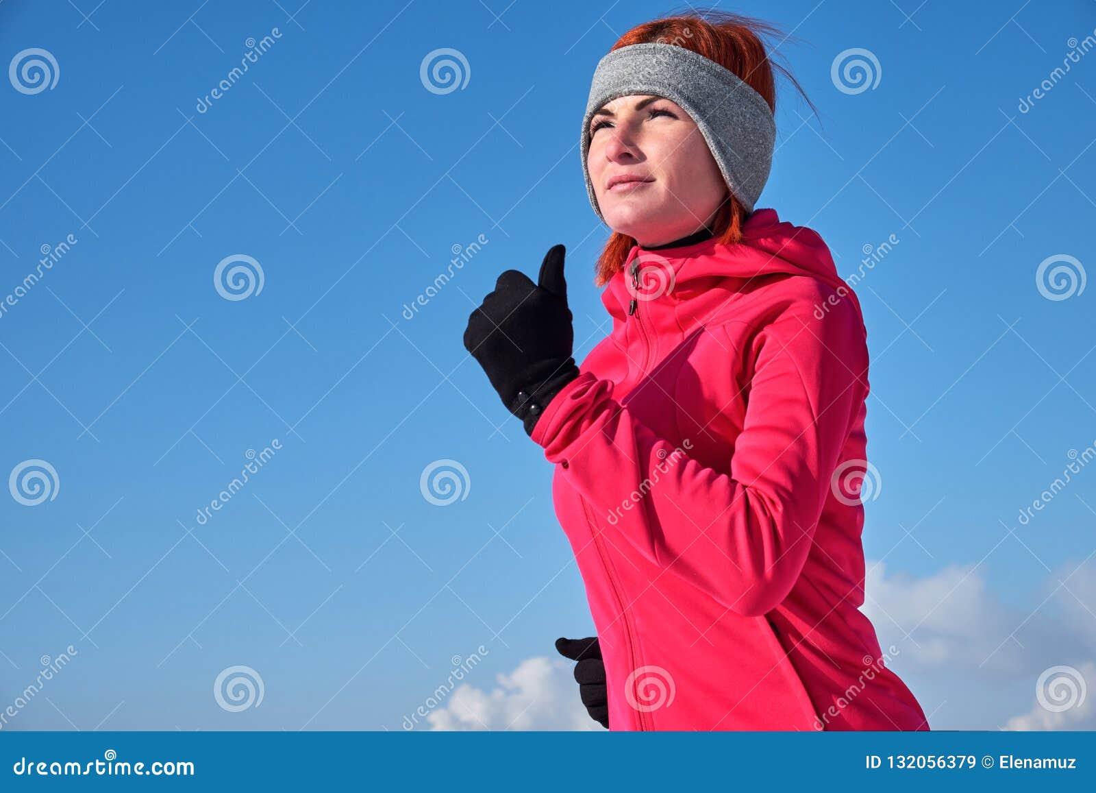 Τρέχοντας αθλήτρια Θηλυκό δρομέων στο κρύο χειμερινό δάσος που φορά το θερμούς φίλαθλους τρέχοντας ιματισμό και τα γάντια