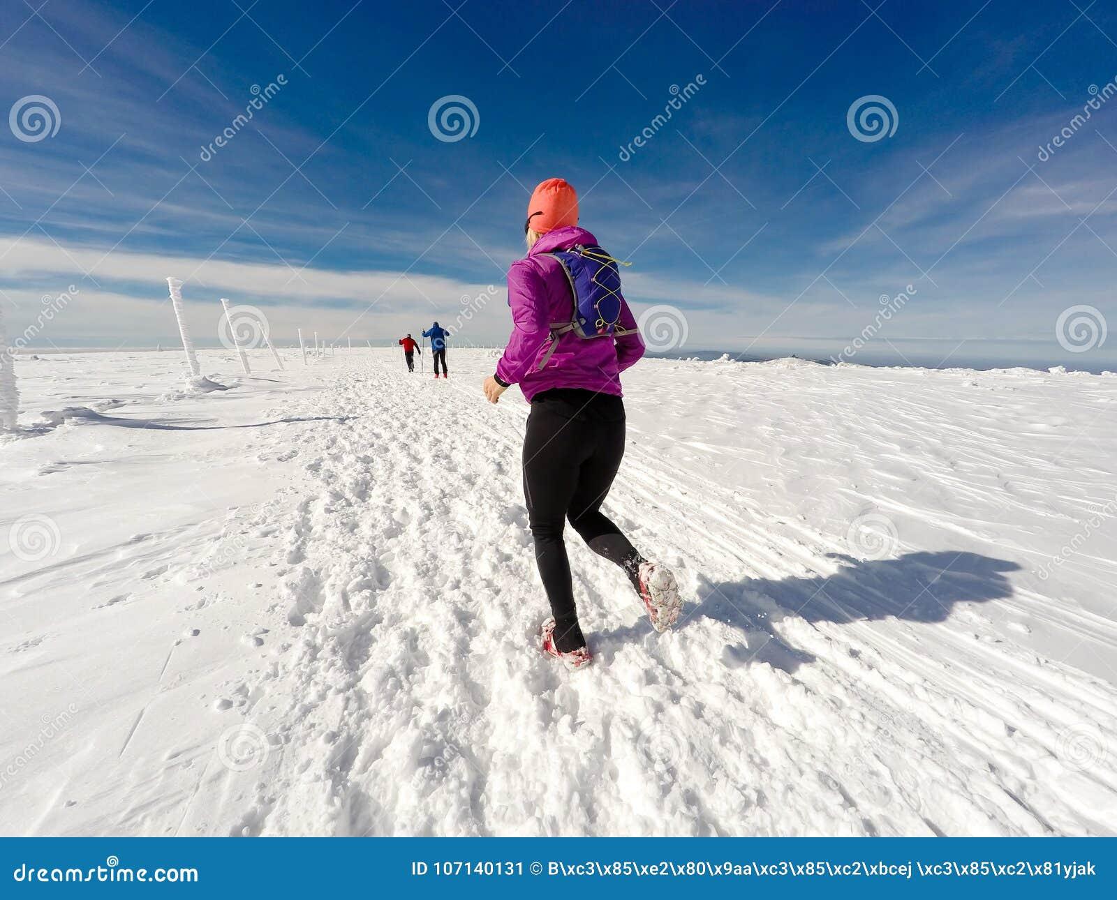 Τρέχοντας γυναίκα στο χειμερινό ίχνος, το χιόνι και τα άσπρα βουνά