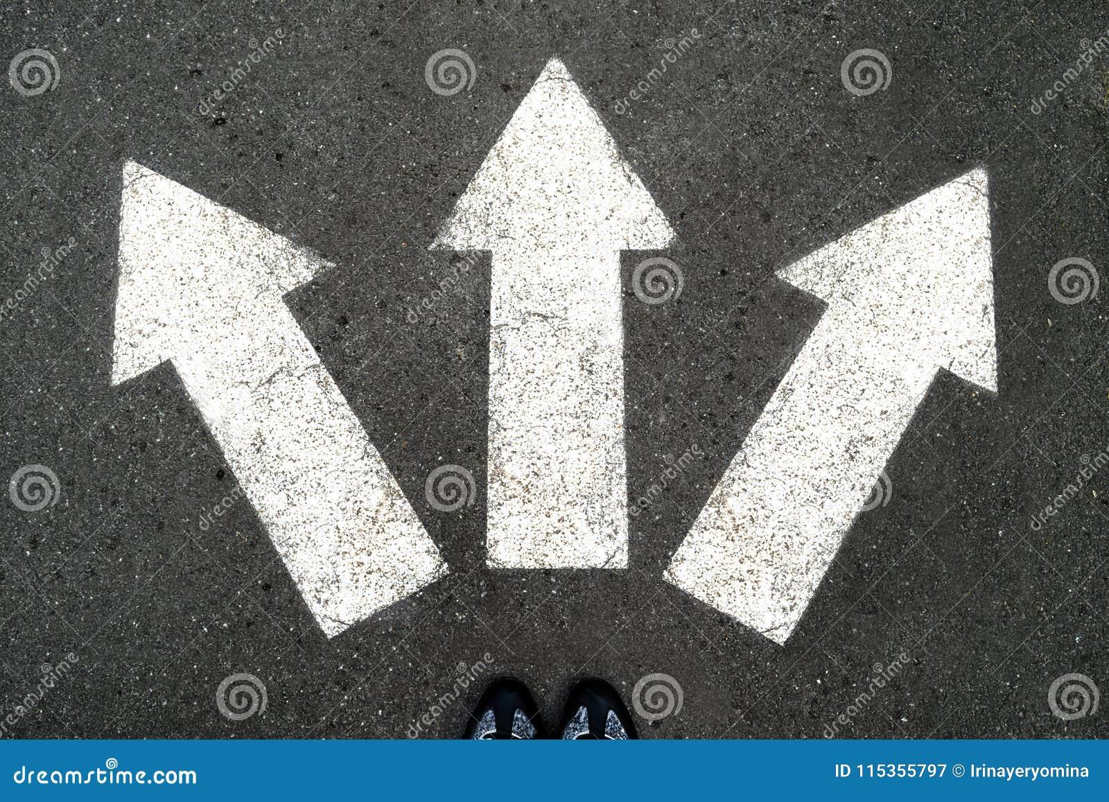 Τρία άσπρα βέλη που δείχνουν στις διαφορετικές κατευθύνσεις στο γκρίζο asph