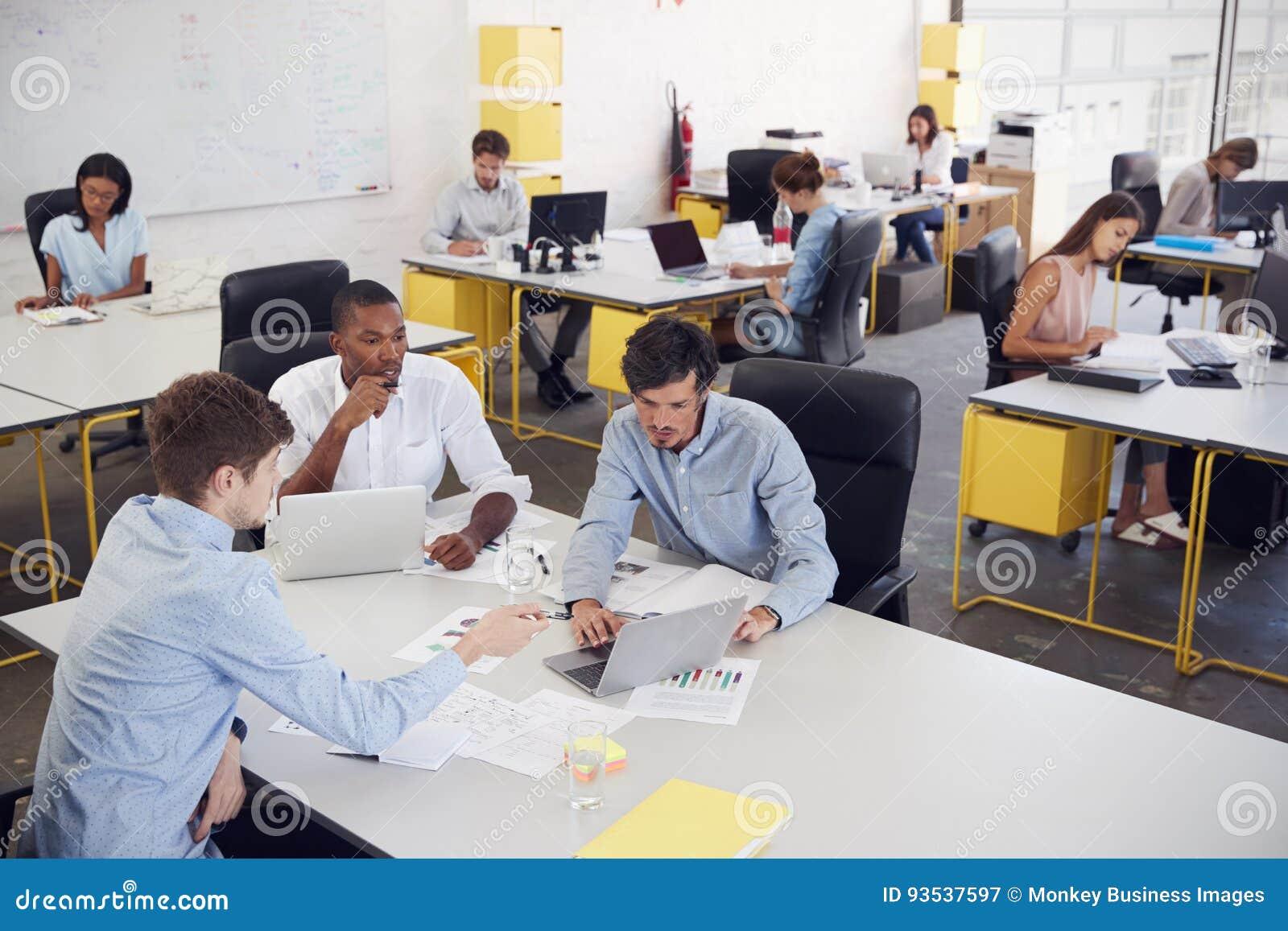 Τρία άτομα που εργάζονται μαζί σε ένα πολυάσχολο γραφείο, ανυψωμένη άποψη