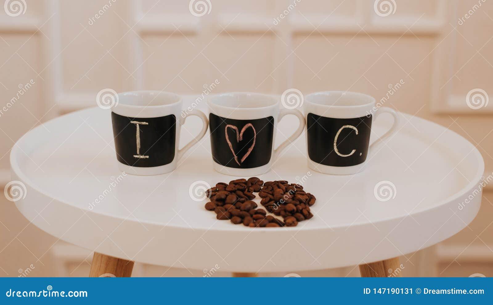 Τρία ίδια μικρά φλυτζάνια καφέ σε μια σειρά που στέκεται στον άσπρο στρογγυλό ξύλινο πίνακα Με το κείμενο Ι καφές αγάπης