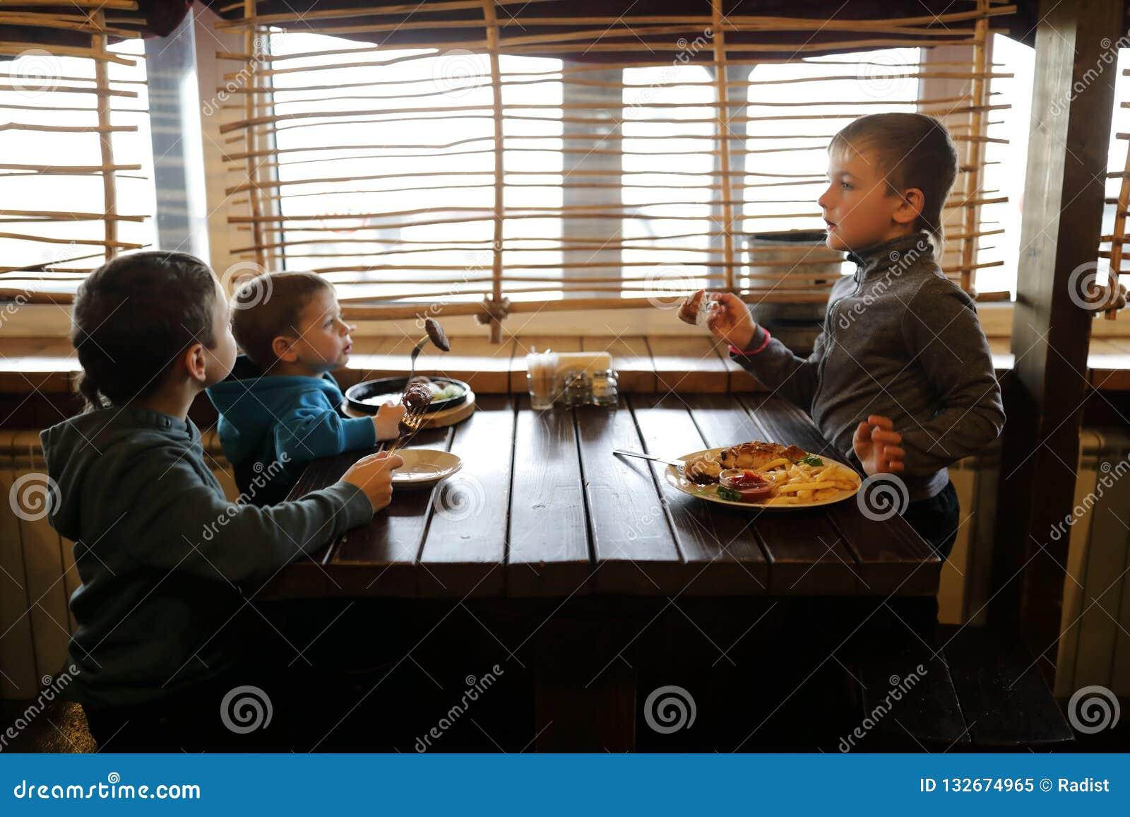 Τρία αγόρια έχουν το μεσημεριανό γεύμα
