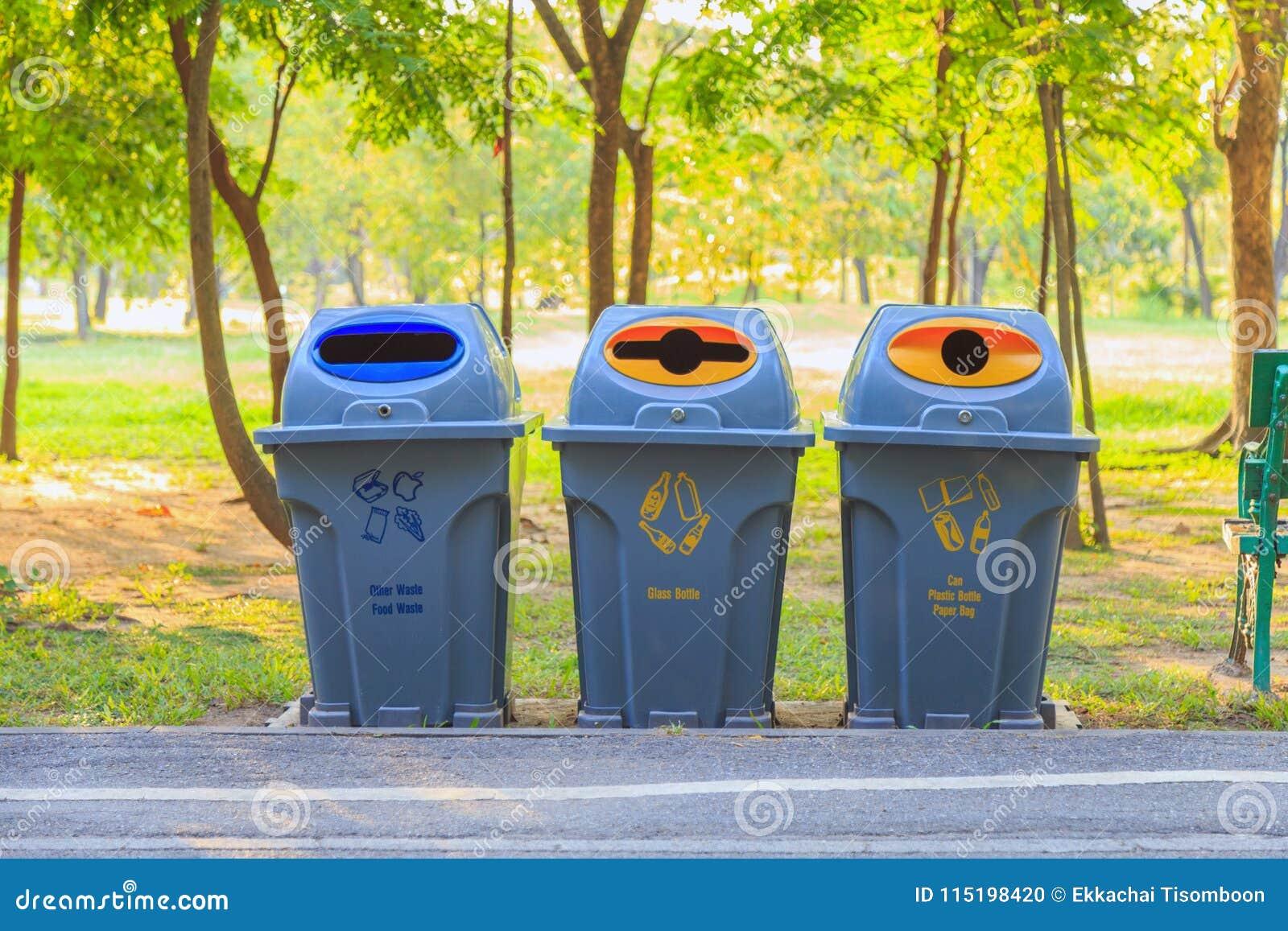 Τρία δοχεία για την ταξινόμηση αποβλήτων κατά μήκος του τρόπου στο πάρκο
