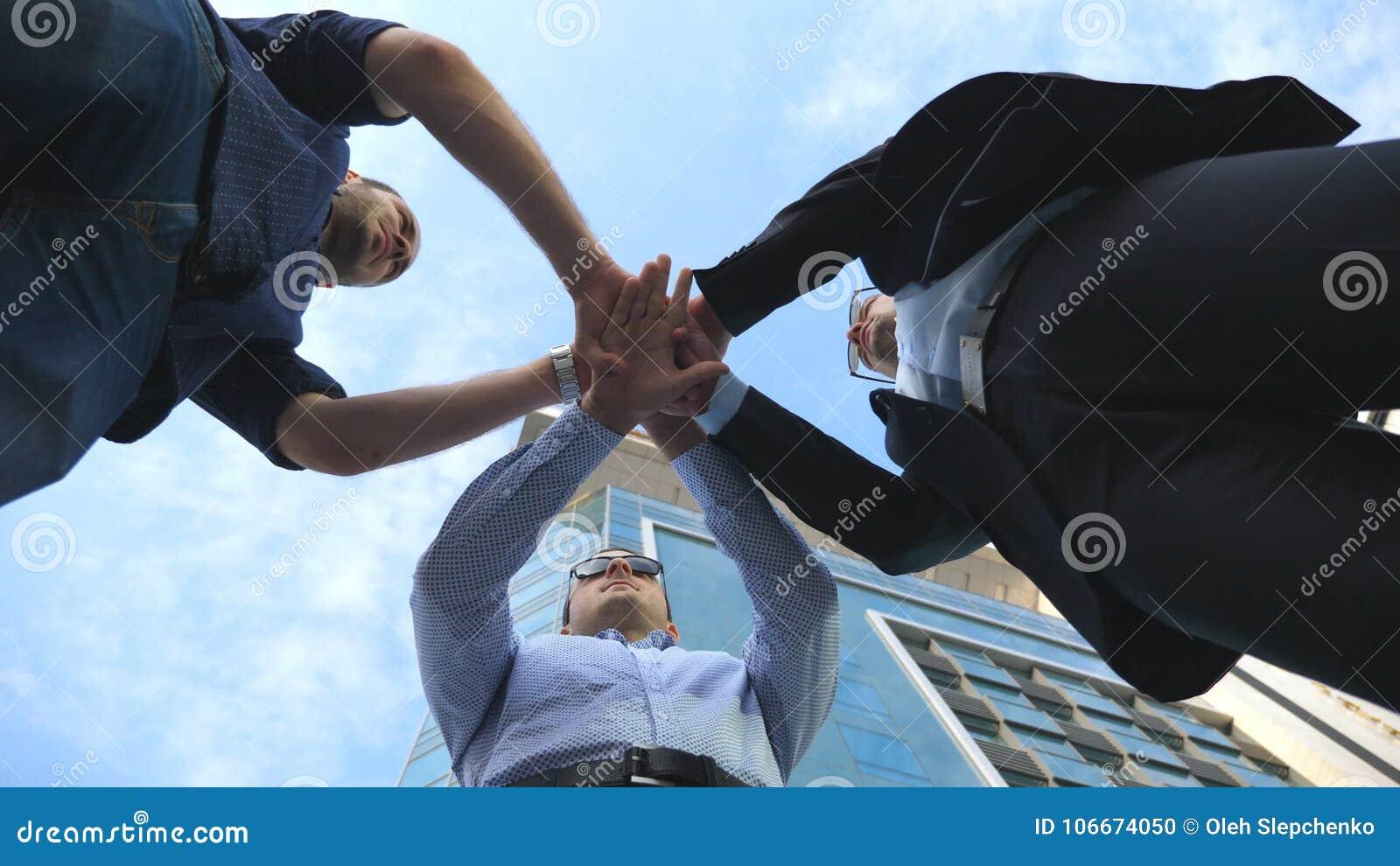 Τρία επιχειρησιακά άτομα που στέκονται το υπαίθριο κοντινό γραφείο και το συσσωρευμένο βραχίονα μαζί στην ενότητα και την ομαδική
