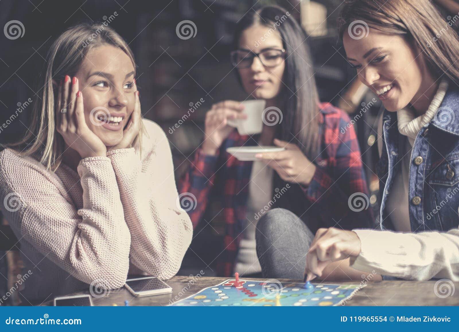 Τρία ευτυχή κορίτσια που παίζουν το επιτραπέζιο παιχνίδι