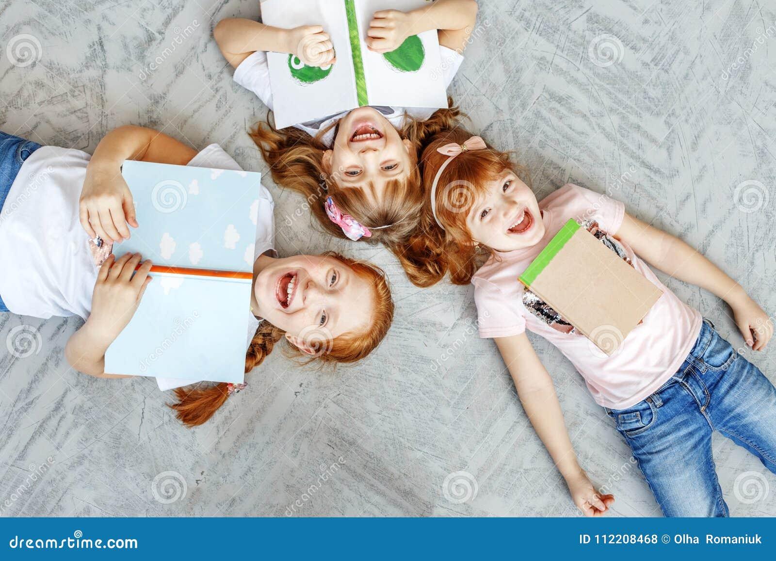 Τρία ευτυχή παιδιά βρίσκονται στο πάτωμα και διαβάζουν τα βιβλία Το concep