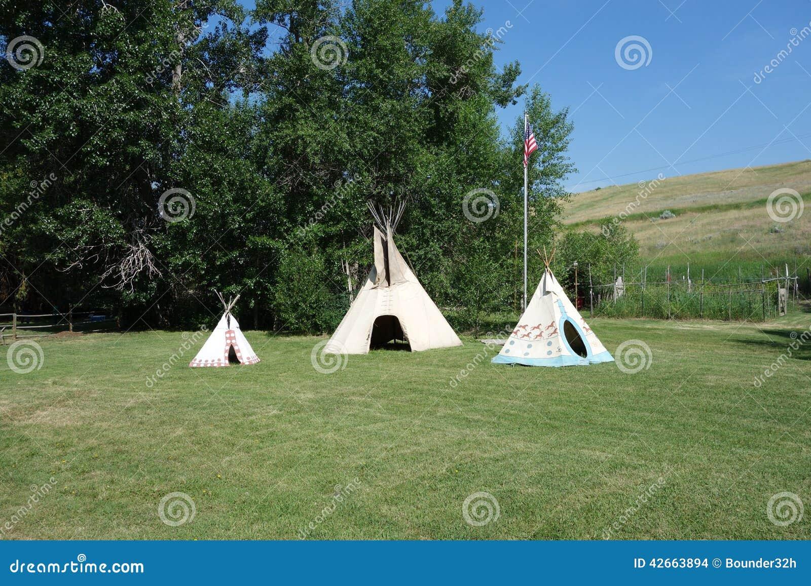 Τρία ινδικά teepees σε έναν χορτοτάπητα στο Idaho