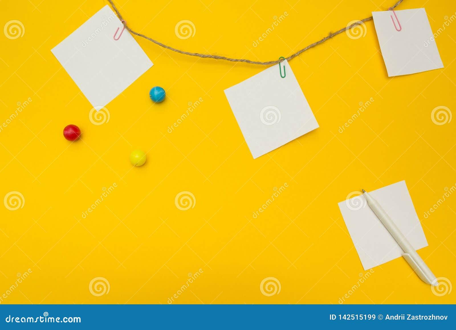 Τρία κενά έγγραφα σημειώσεων που συνδέονται με ένα σχοινί σε ένα κίτρινο υπόβαθρο Επίπεδη σύνθεση