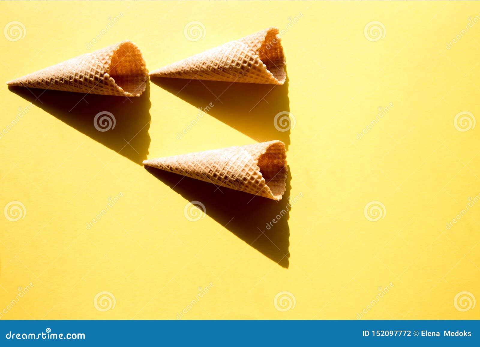 Τρία κενά φλυτζάνια βαφλών για το παγωτό σε ένα κίτρινο υπόβαθρο στο φωτεινό φως του ήλιου και τις τραγανές, σκληρές σκιές r