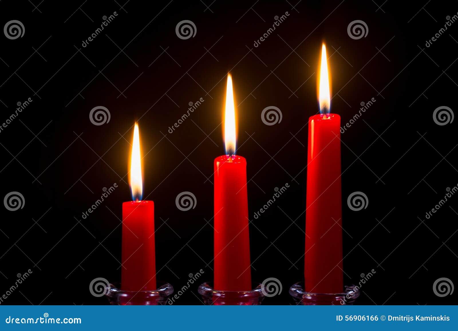 Τρία κόκκινα κεριά σε ένα μαύρο υπόβαθρο