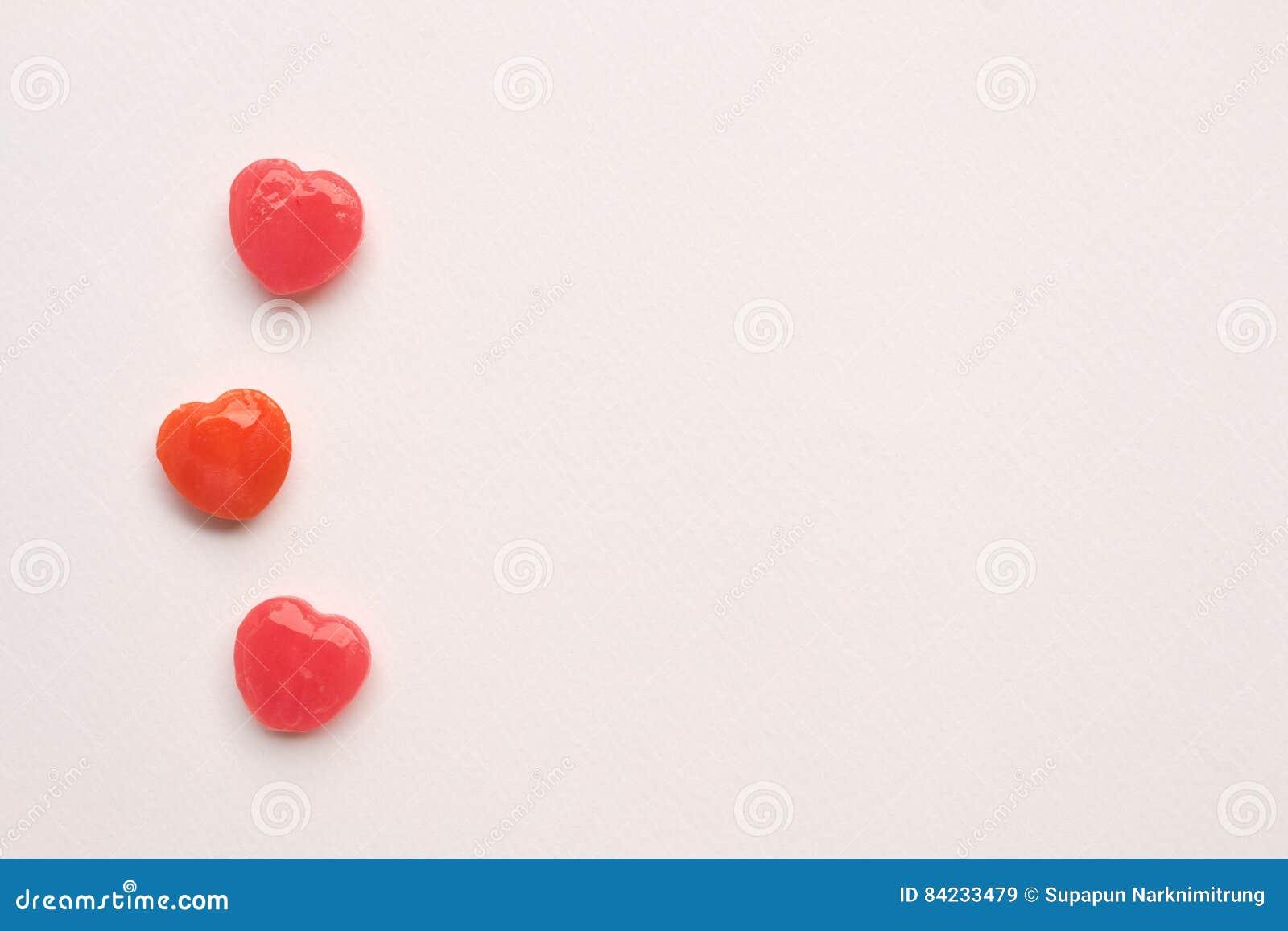 Τρία κόκκινη γραμμή καραμελών μορφής καρδιών ημέρας βαλεντίνων ` s στο υπόβαθρο της Λευκής Βίβλου άνδρας αγάπης φιλιών έννοιας στ