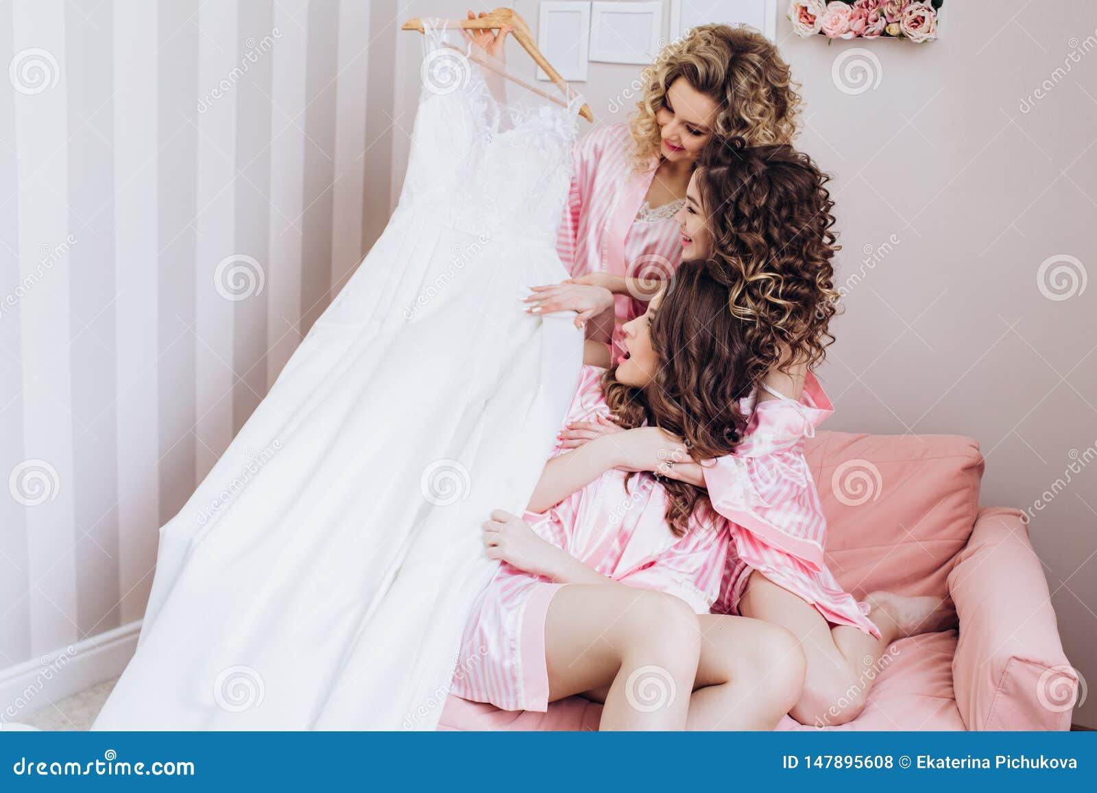 Τρία λεπτά, νέα, όμορφα κορίτσια στις ρόδινες πυτζάμες εξετάζουν ένα γαμήλιο φόρεμα