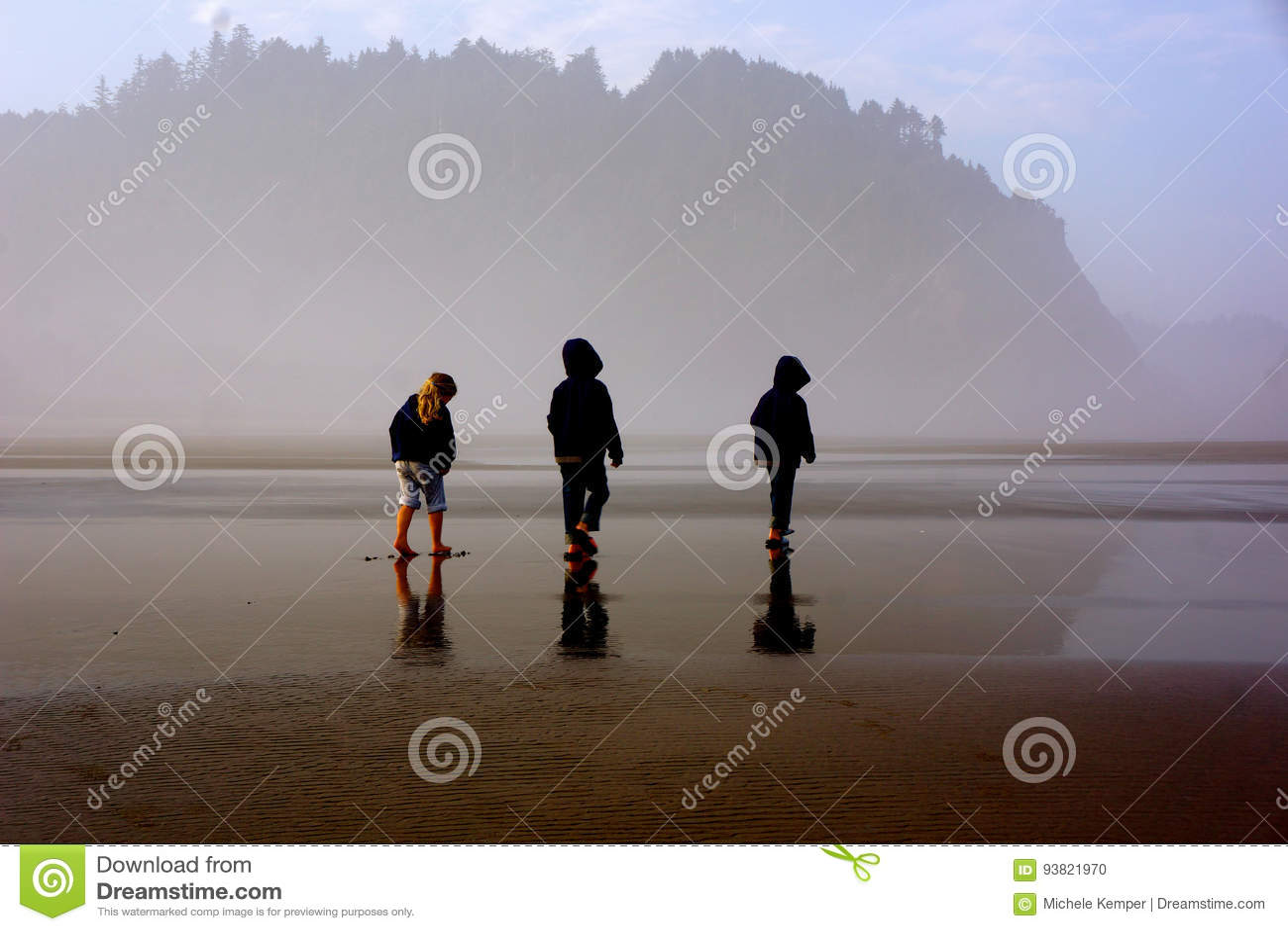 Τρία μικρά παιδιά στη misty παραλία