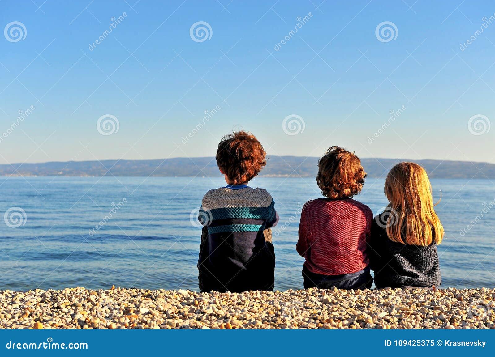 Τρία παιδιά που κάθονται στην παραλία