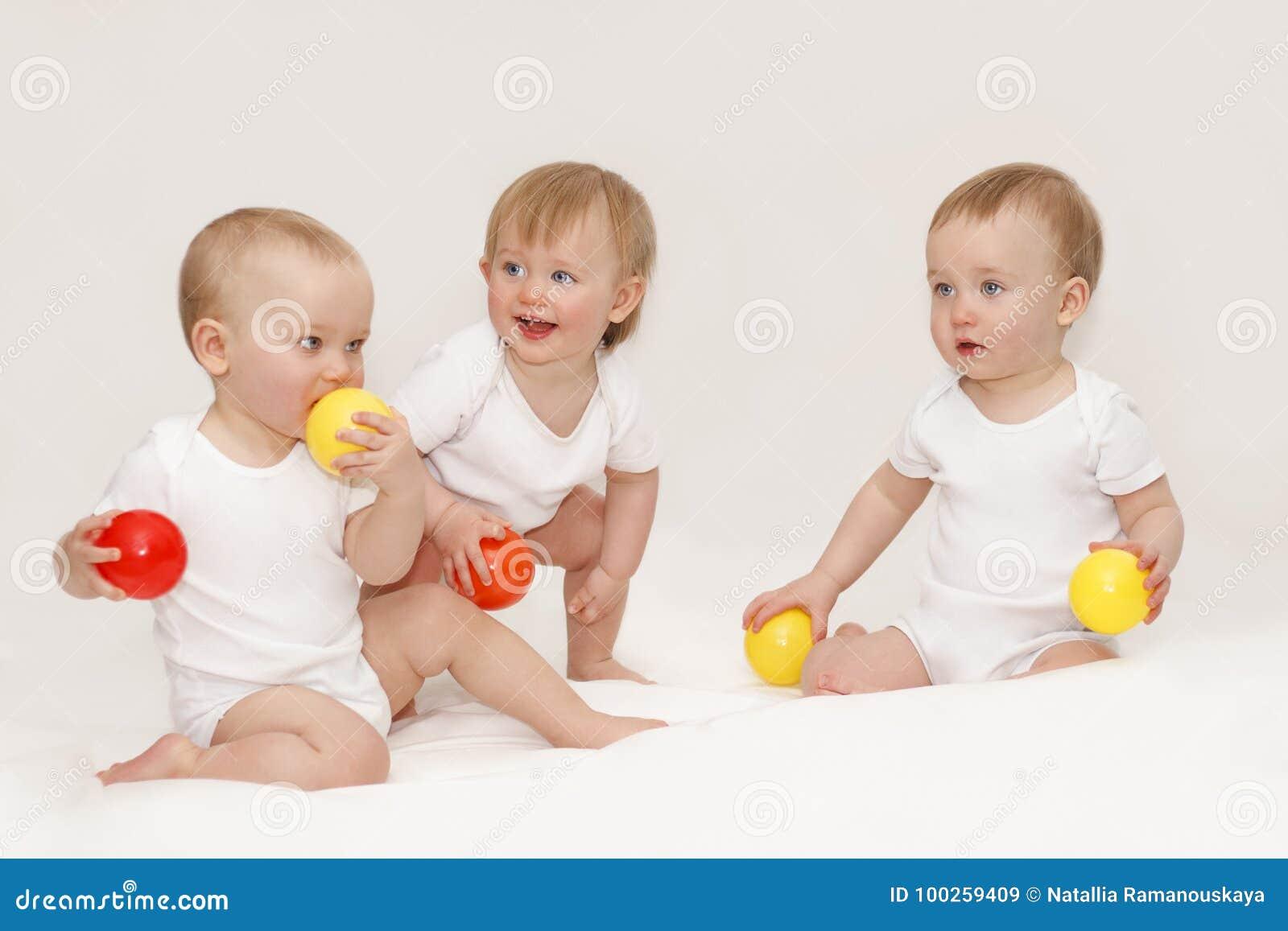 cb03584d9df8 Τρία παιδιά κάθονται στις άσπρες μπλούζες σε ένα άσπρο υπόβαθρο παιχνίδι  τρίδυμων σε ένα άσπρο υπόβαθρο