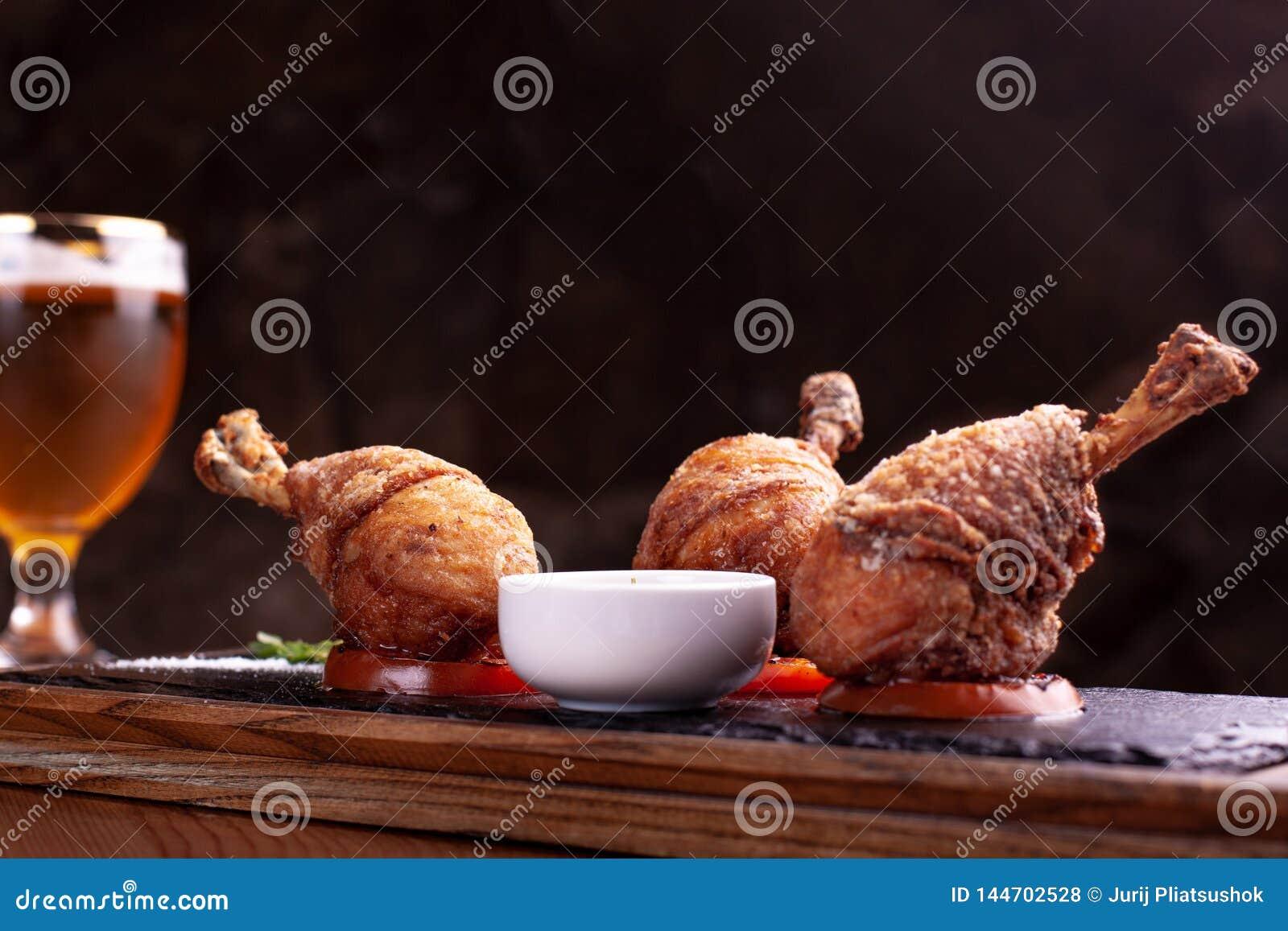Τρία πασπαλισμένα με ψίχουλα πόδια κοτόπουλου στις σαλτσιέρες, στάση στη μαύρη πλάκα Μαύρο υπόβαθρο, όμορφο φως
