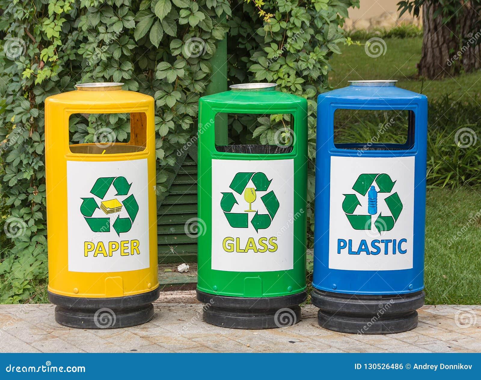 Τρία πολύχρωμα ανακύκλωσης δοχεία για τα απόβλητα με τα εικονίδια για διευκόλυνση της ταξινόμησης των παλιοπραγμάτων σπαταλούν στ