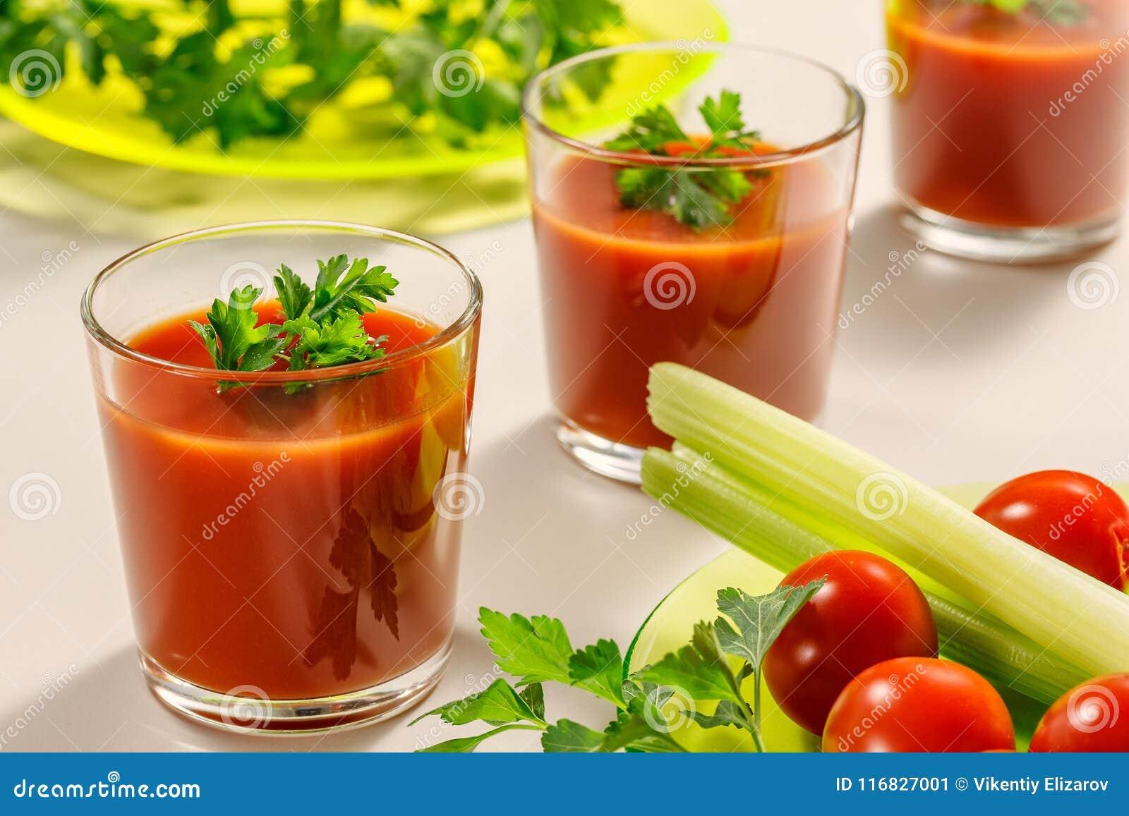 Τρία ποτήρια του χυμού ντοματών που διακοσμούνται με τα φύλλα μαϊντανού ή κορίανδρου Έπειτα είναι ένα πιάτο του μαϊντανού, των ντ
