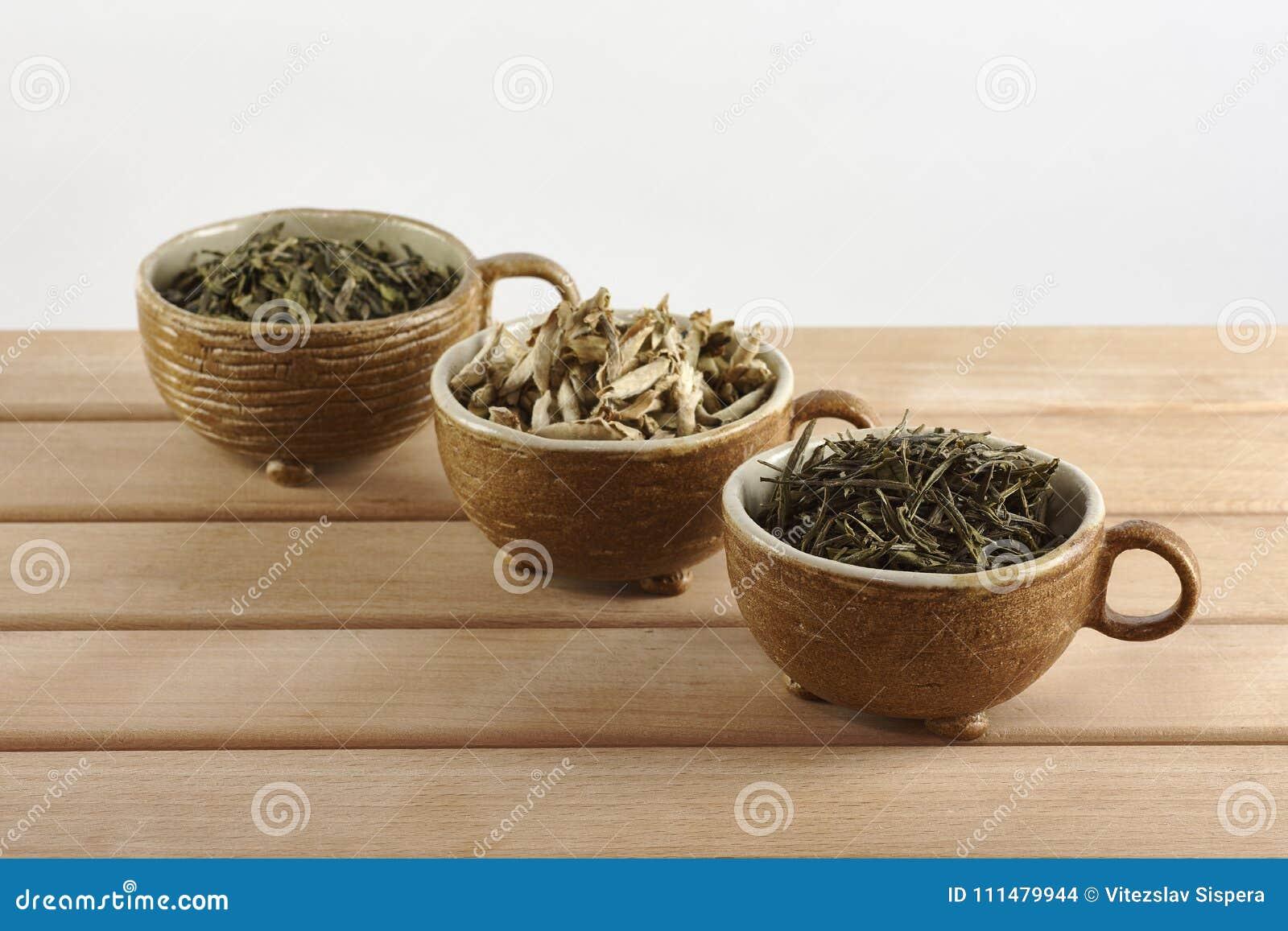 Τρία φλυτζάνια με τα πράσινα φύλλα τσαγιού σε ένα άσπρο υπόβαθρο