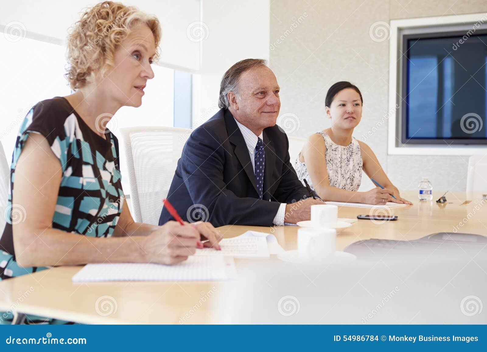 Τρία Businesspeople που διοργανώνουν τη συνεδρίαση στην αίθουσα συνεδριάσεων