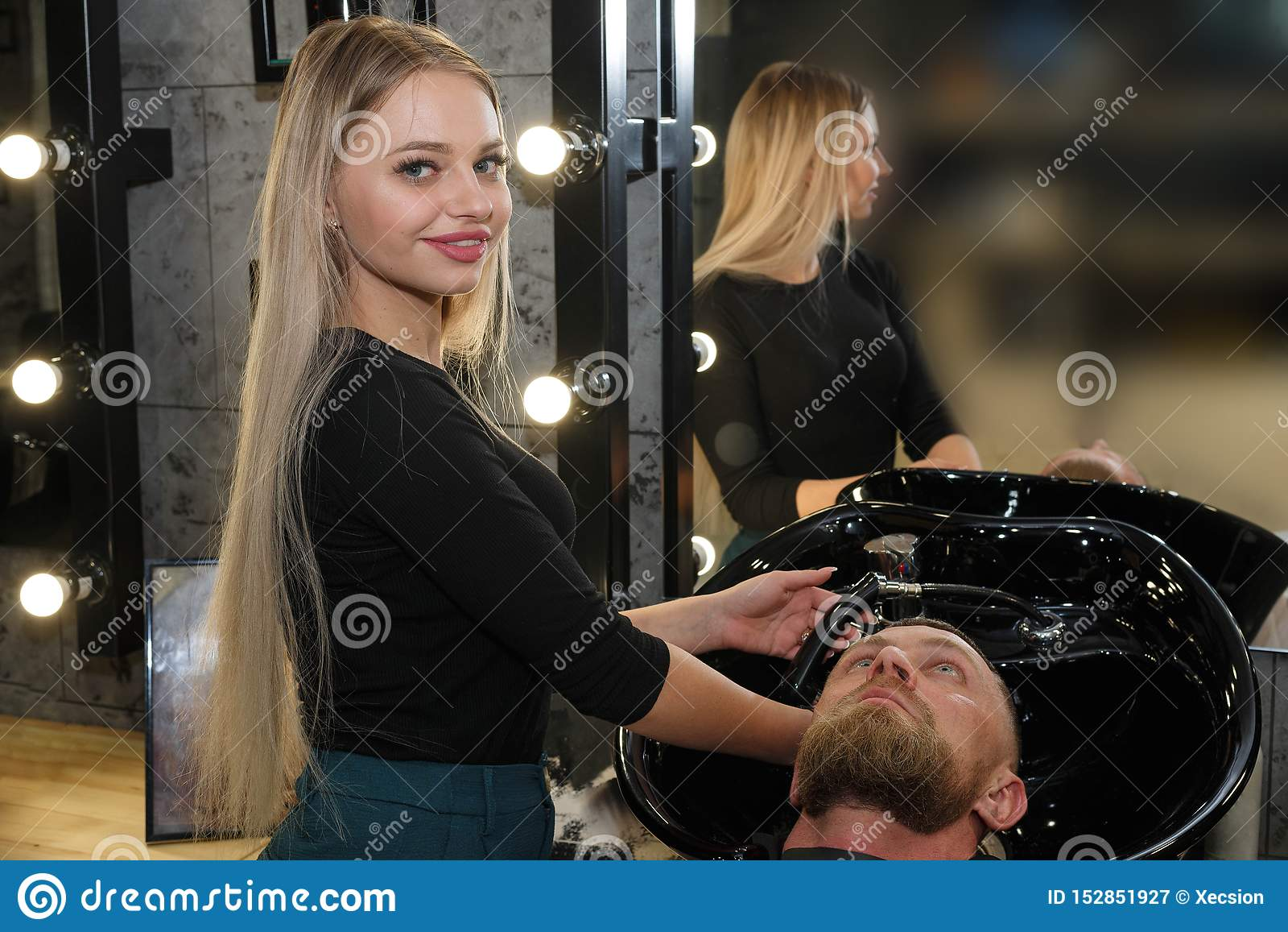Τρίχα του πελάτη πλύσης Hairstylist στο κατάστημα κουρέων