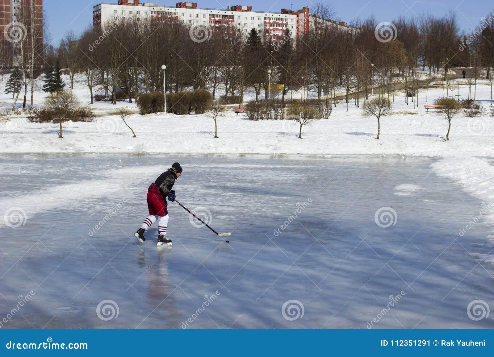 Τραίνα χόκεϋ παικτών στον πάγο Ένα πλυντήριο με ένα ραβδί στη λίμνη