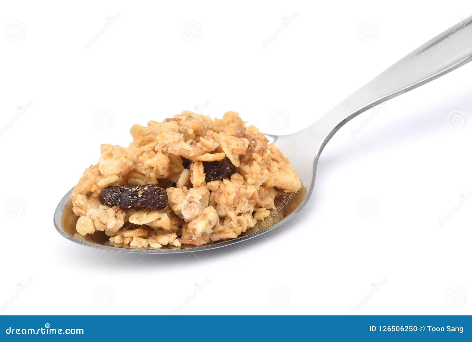 Τραγανά δημητριακά granola βρωμών με τους ξηρούς καρπούς στο ανοξείδωτο κουτάλι