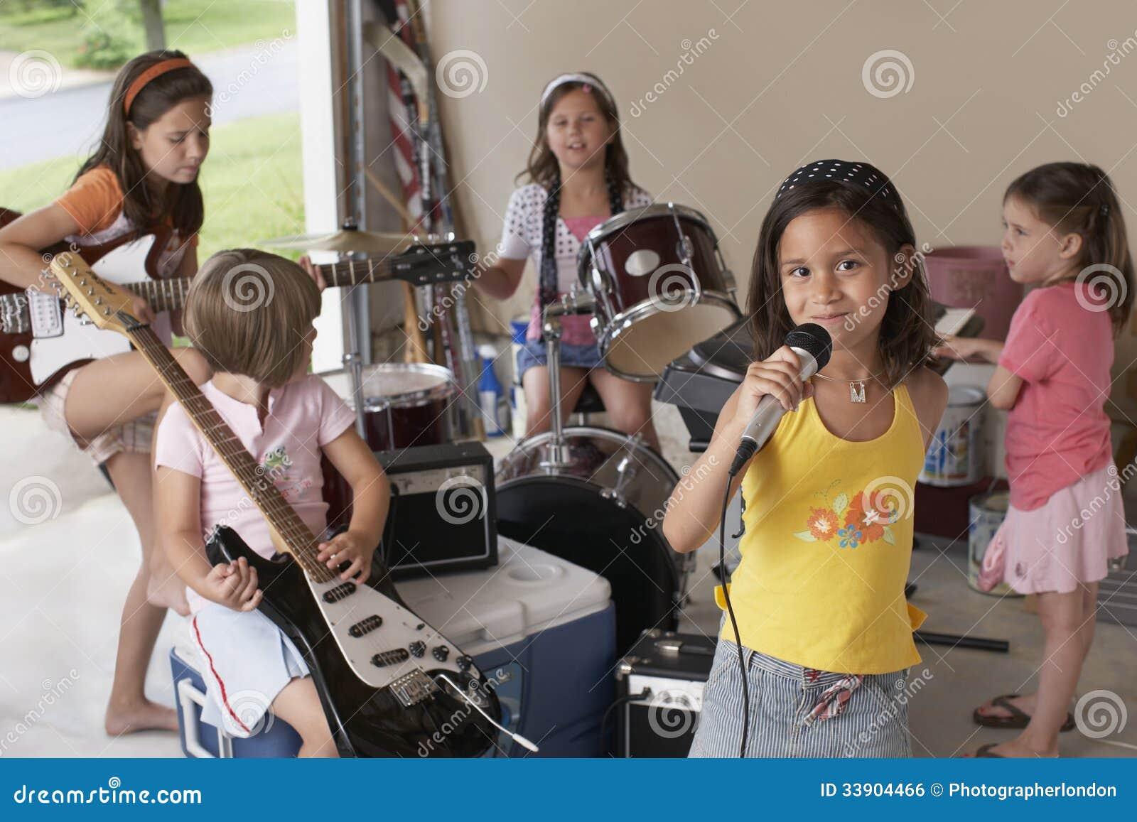 Τραγούδι κοριτσιών στο μικρόφωνο με τους φίλους που παίζουν το μουσικό όργανο