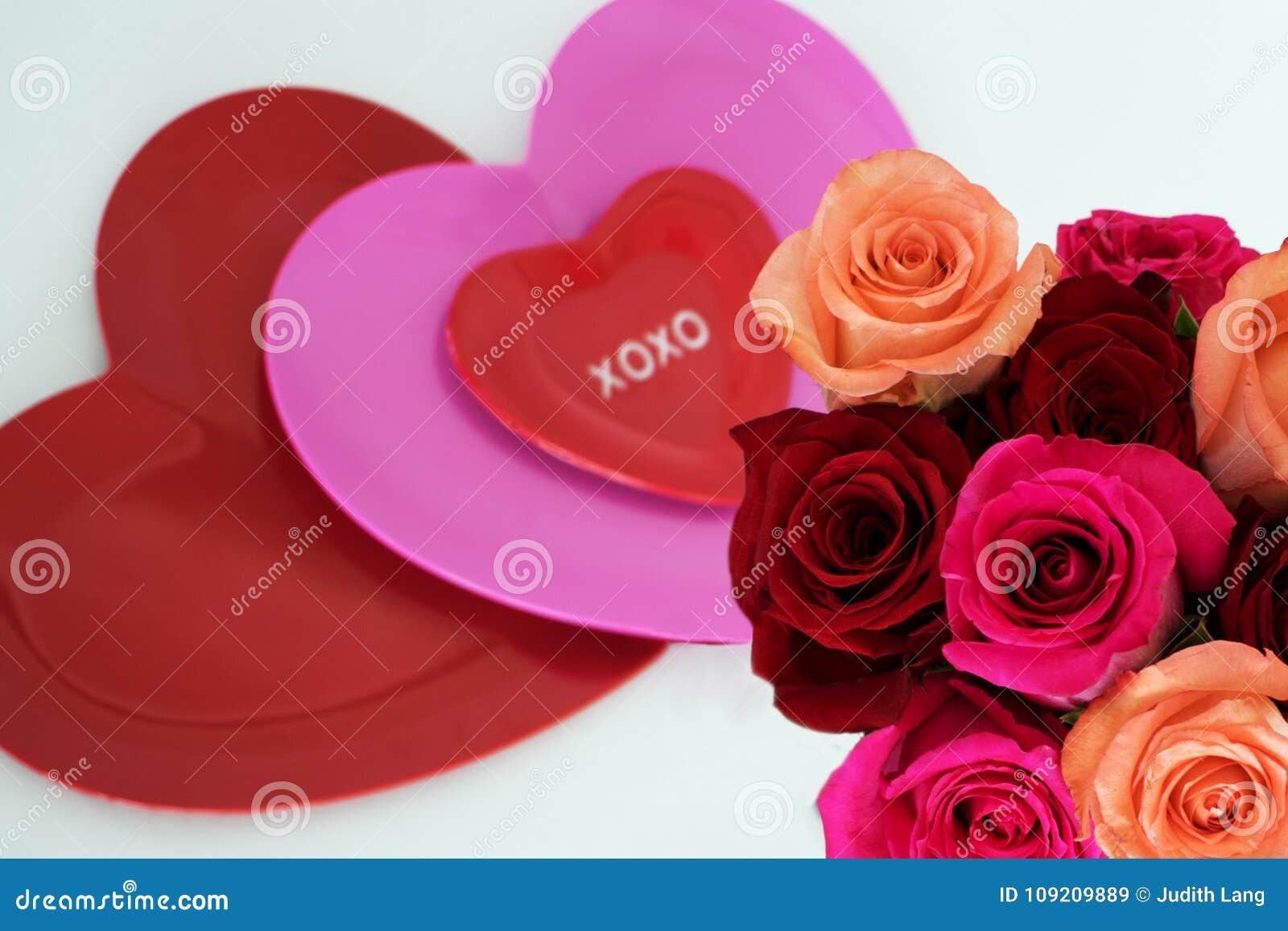 Τρεις καρδιές στο κέντρο με την ανθοδέσμη των τριαντάφυλλων στο χαμηλότερο δικαίωμα