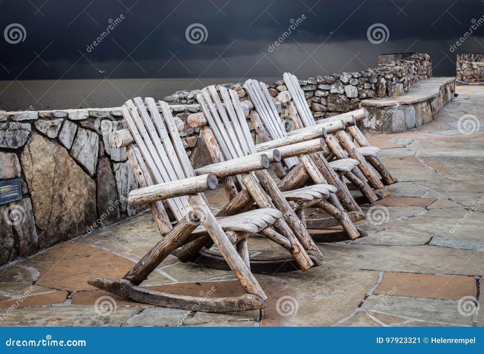 Τρεις ξύλινες λικνίζοντας καρέκλες που κάθονται στο μαξιλάρι τσιμέντου