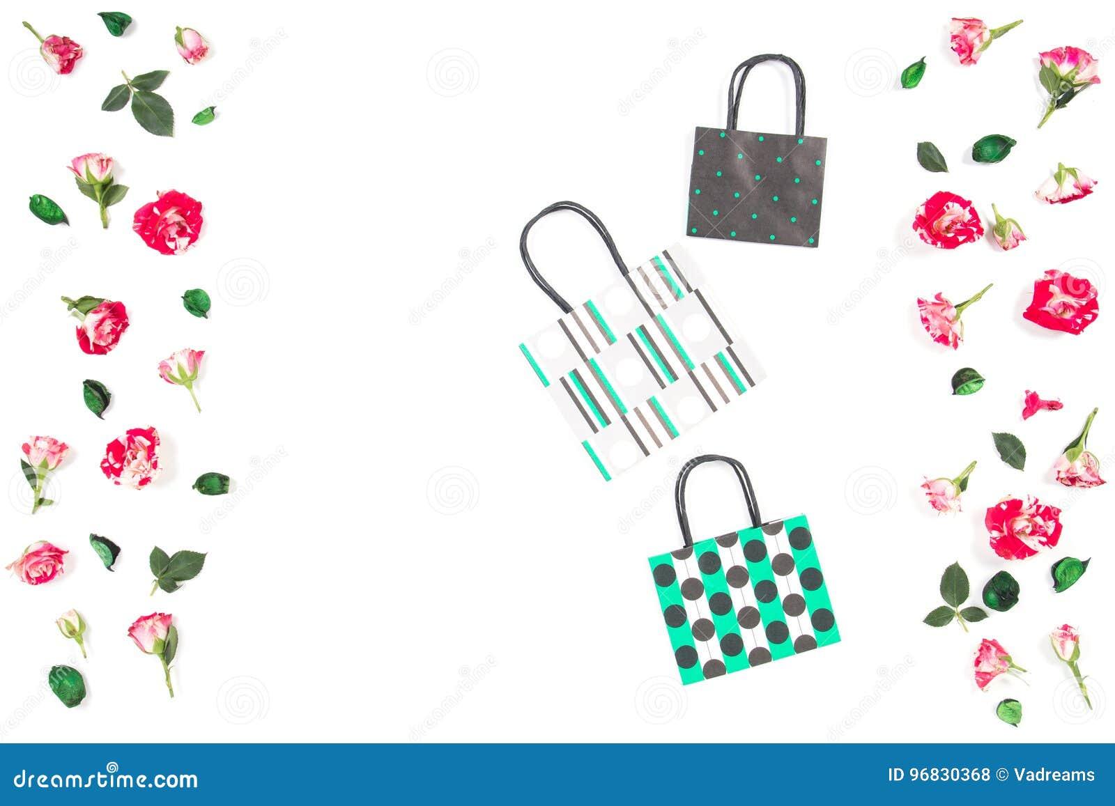 6ee4703f2c Τρεις ζωηρόχρωμες τσάντες αγορών εγγράφου και αυξήθηκαν πλαίσιο λουλουδιών  στο άσπρο υπόβαθρο Τοπ όψη