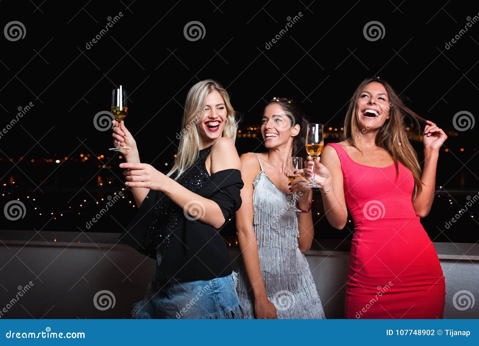 Τρεις όμορφες, εύθυμες γυναίκες που έχουν μια νύχτα κοριτσιών έξω, έχοντας τη διασκέδαση