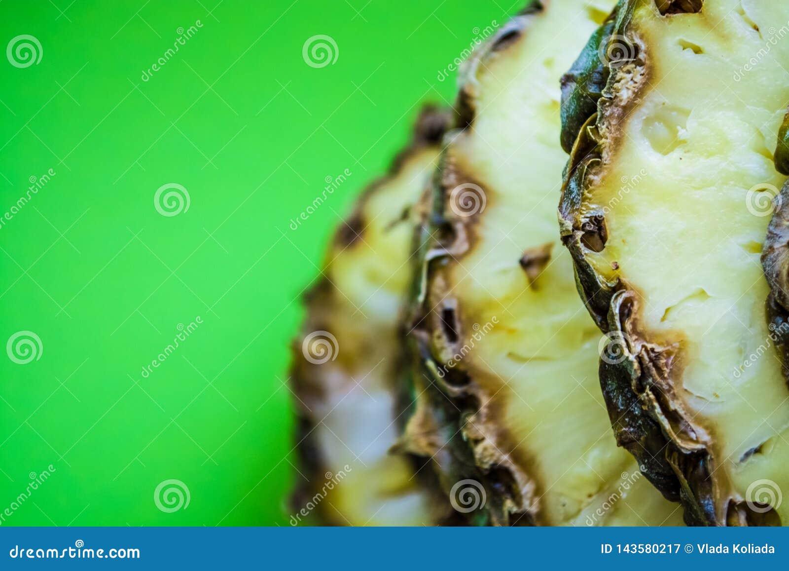 Τροπικό εσπεριδοειδές ο ανανάς που κόβεται στα δαχτυλίδια σε ένα πράσινο υπόβαθρο r Εξωτικός του καλοκαιριού