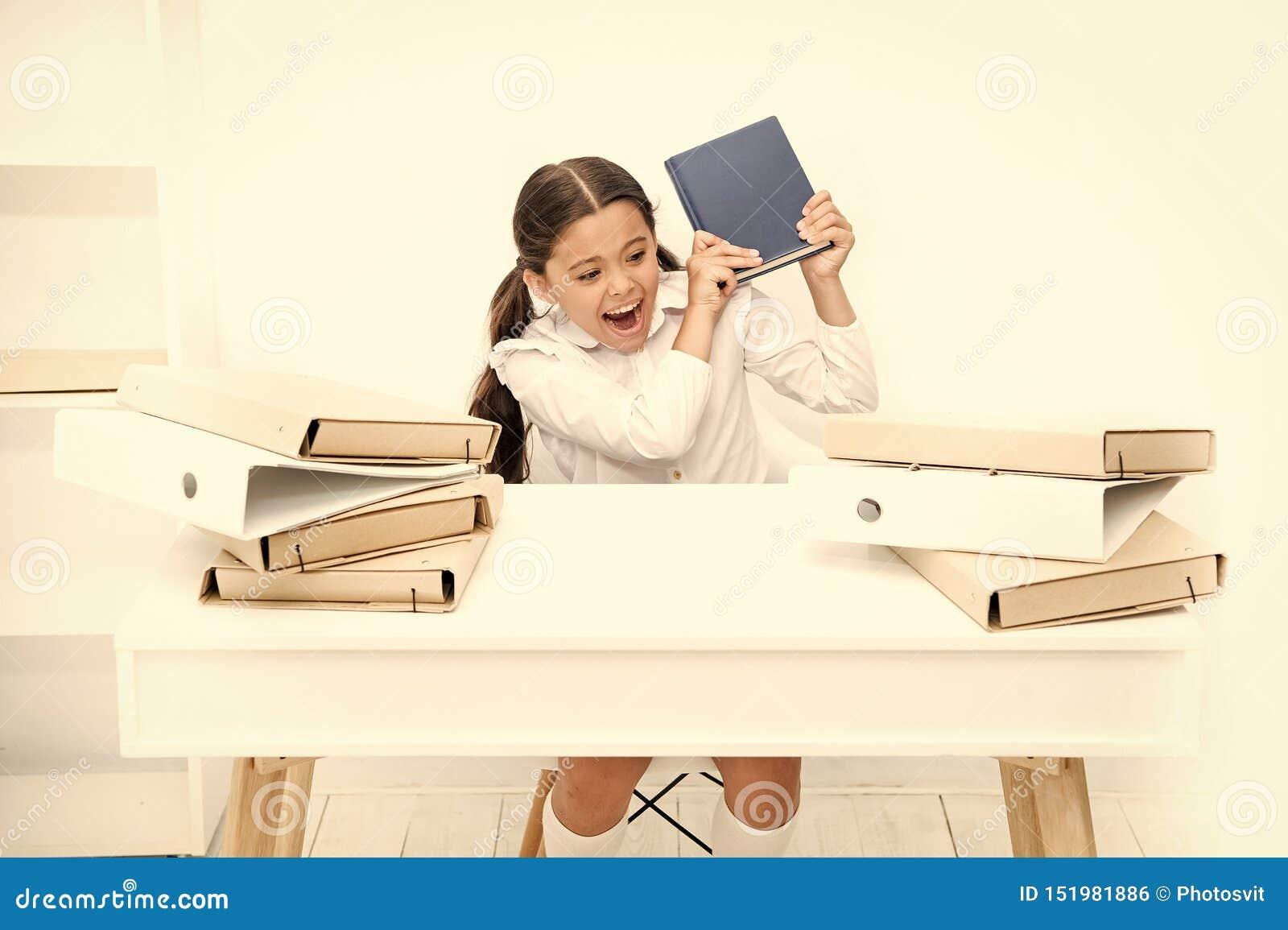 Τρυπημένος ο κορίτσι μαθητής κάθεται στο γραφείο με τους φακέλλους και τα βιβλία Ζητήματα της βασικής εκπαίδευσης E Χαριτωμένος π