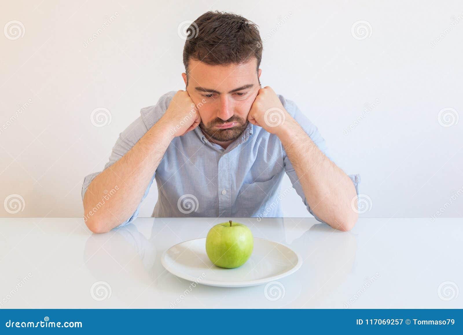 Τρυπημένο άτομο που τρώει μόνο ένα μήλο για τη διατροφή