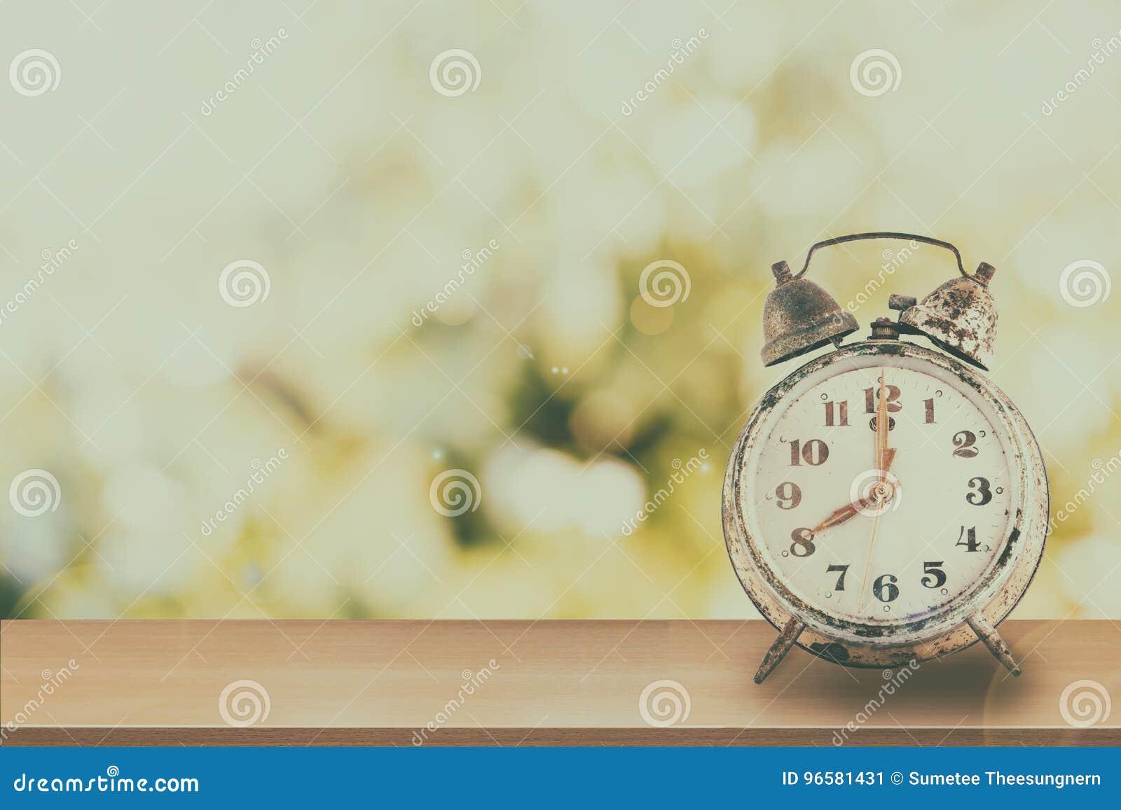 Τρύγος του αναδρομικού ξυπνητηριού στην ξύλινη επιτραπέζια φύση και το πράσινο BO