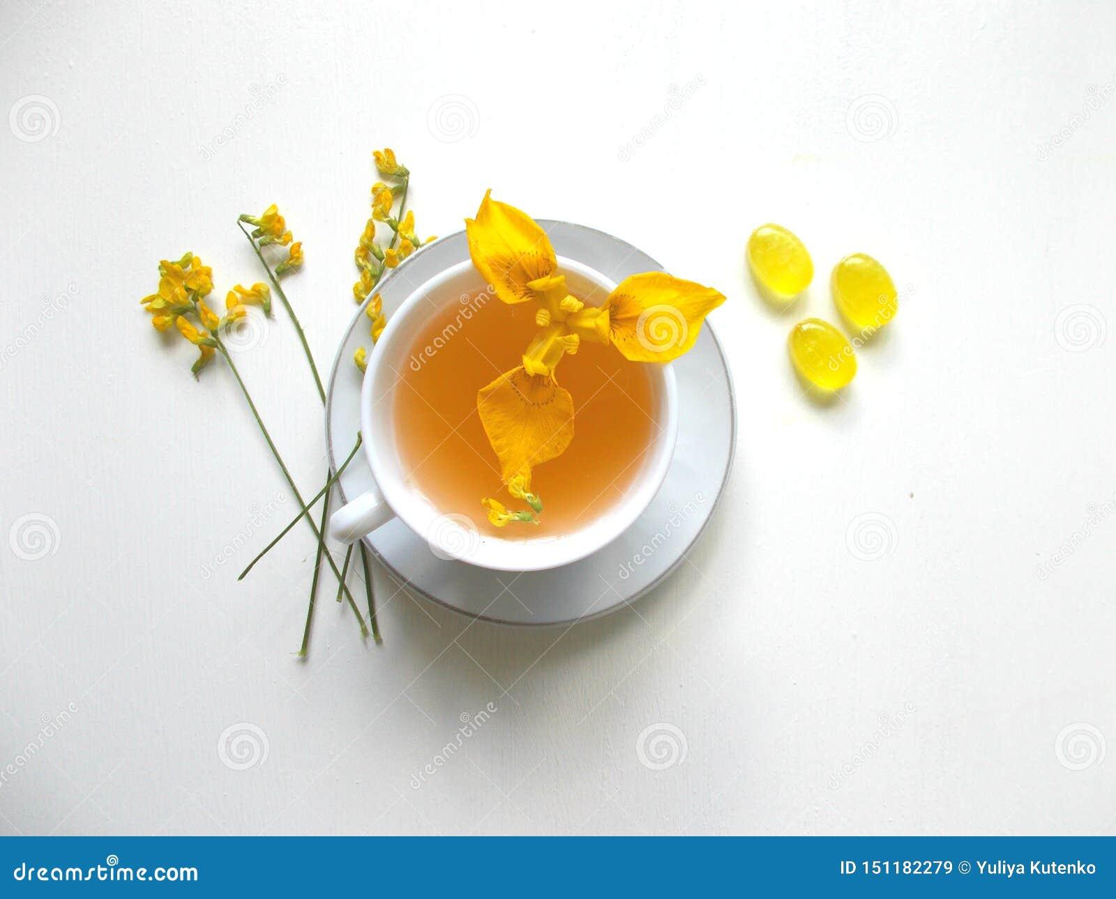 Τσάι σε ένα άσπρο φλυτζάνι με τα κίτρινα λουλούδια