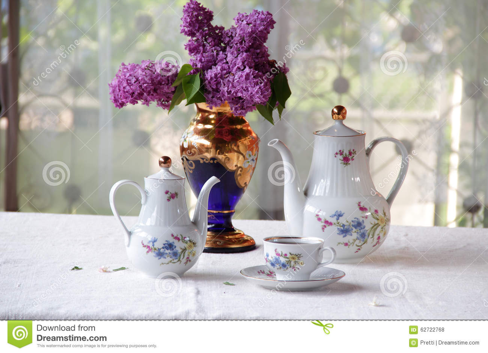 Τσάι σε ένα φλυτζάνι, και μια ιώδης ανθοδέσμη σε έναν πίνακα