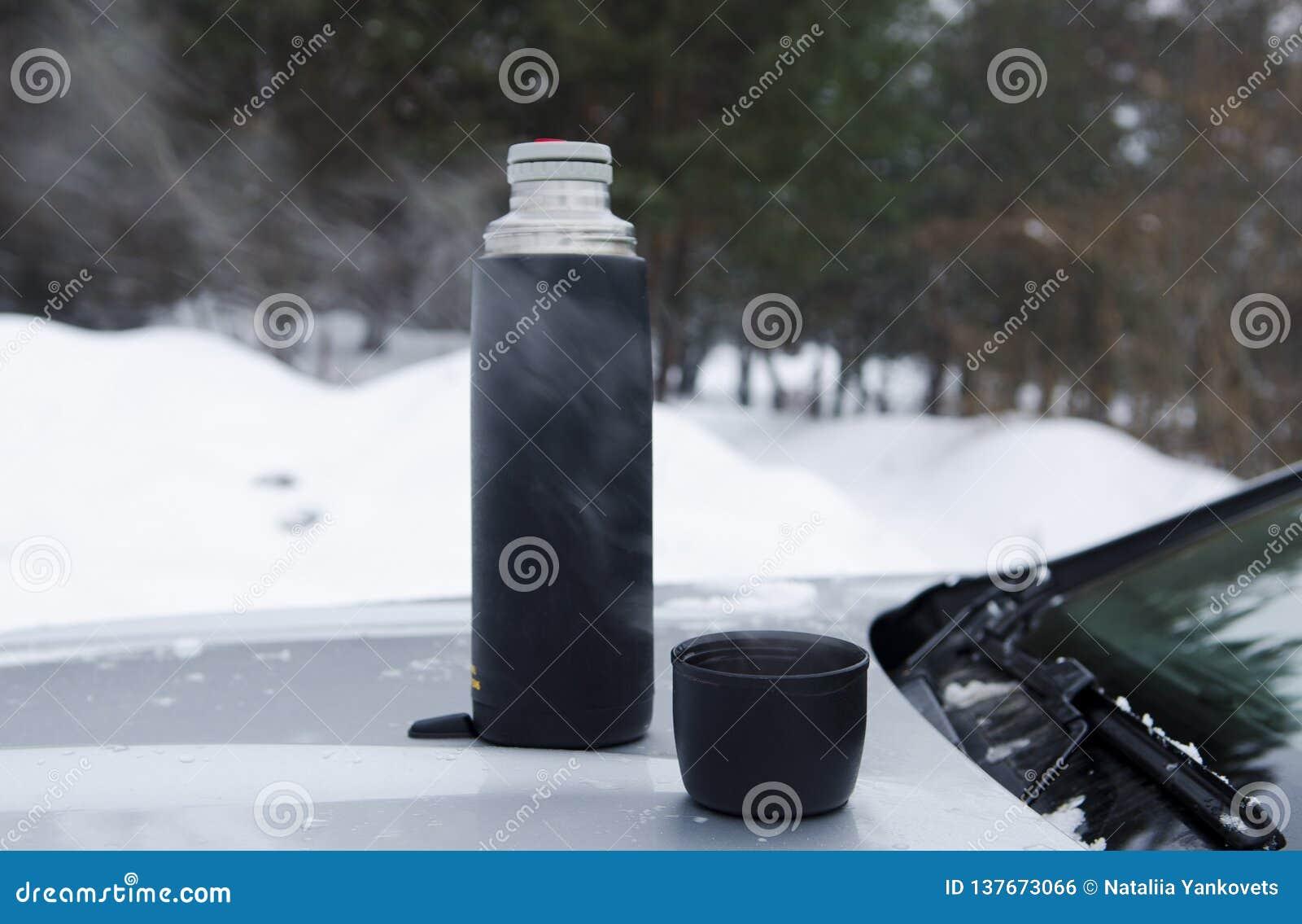 Τσάι χειμερινών πικ-νίκ στην κουκούλα της μηχανής ενάντια στο σκηνικό του δάσους
