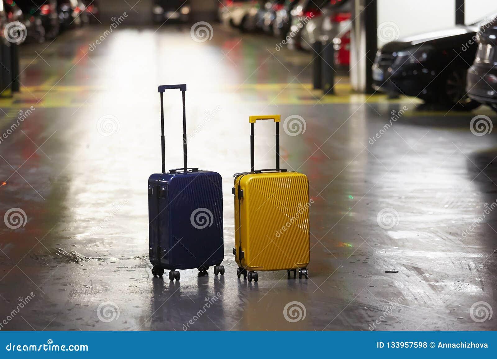 Τσάντα αποσκευών στην οδό πόλεων έτοιμη να επιλέξει με το αυτοκίνητο ταξί μεταφοράς αερολιμένων